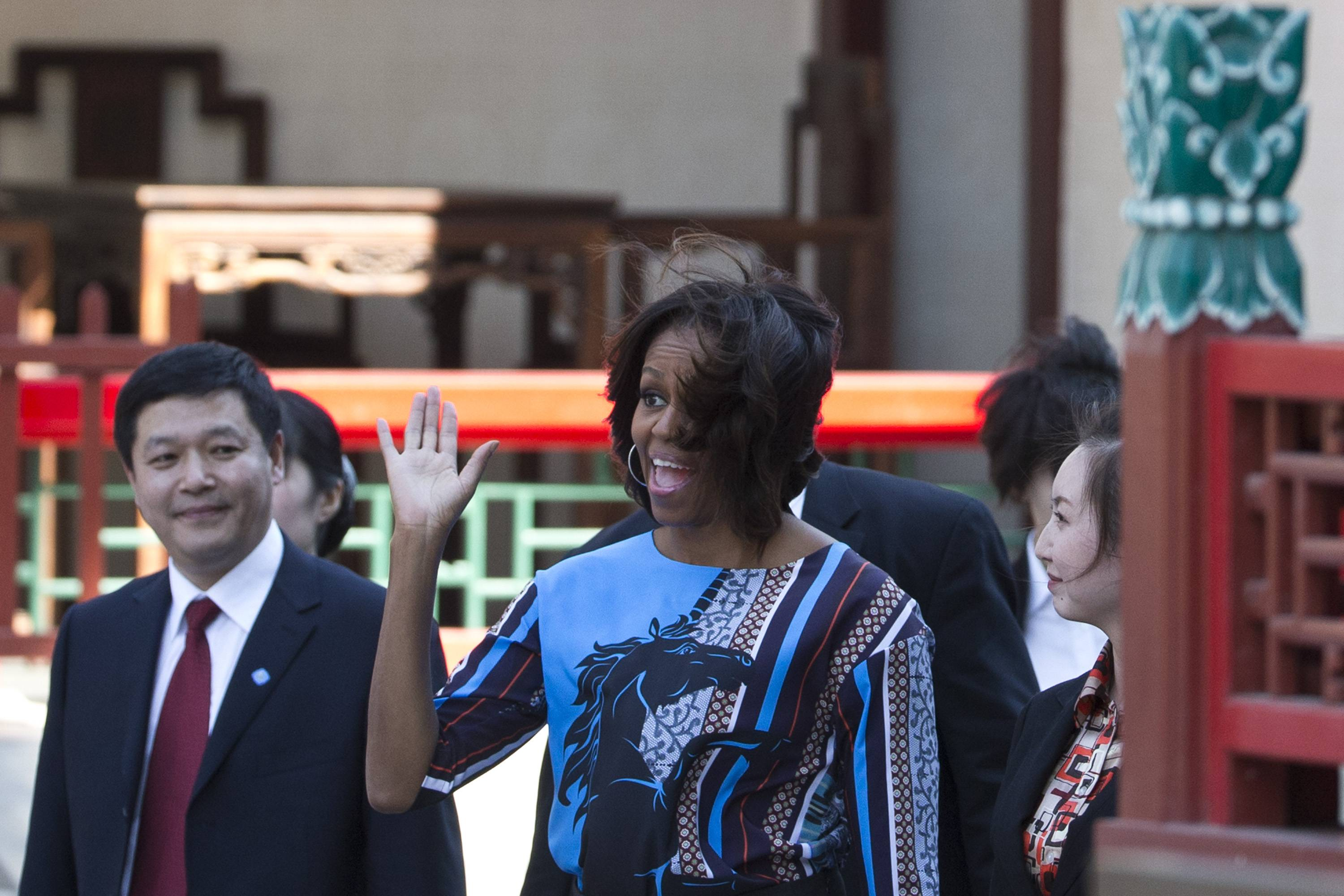 U.S. first lady Michelle Obama waves to a group of American schoolchildren Saturday who are visiting China during their spring break before they watch a Peking opera performance at the Summer Palace in Beijing.
