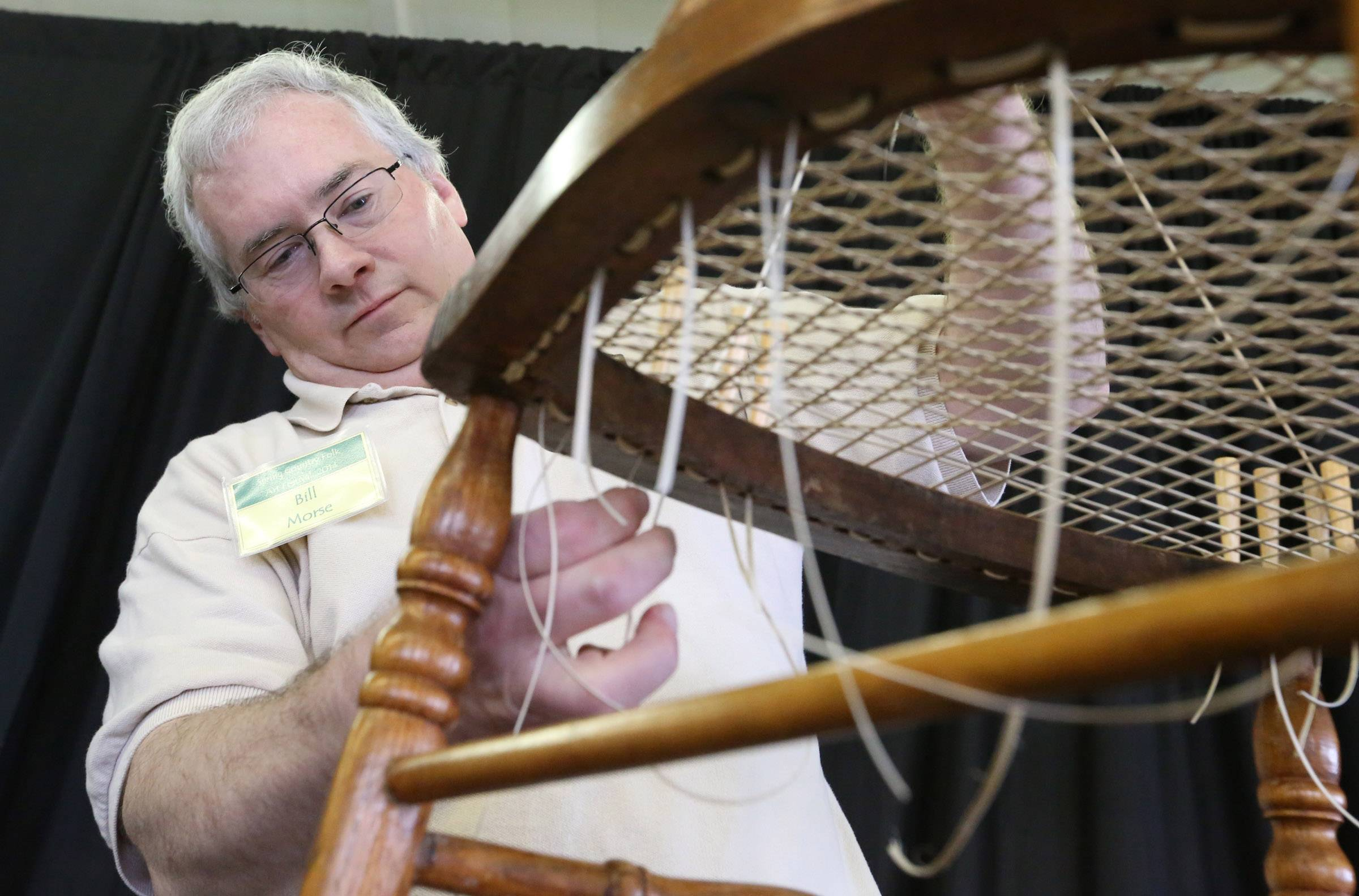 Bill Morse of Elgin weaves a seat for a wooden chair during a Spring Country Folk Art Festival at Kane County Fairgrounds on Saturday in St. Charles.