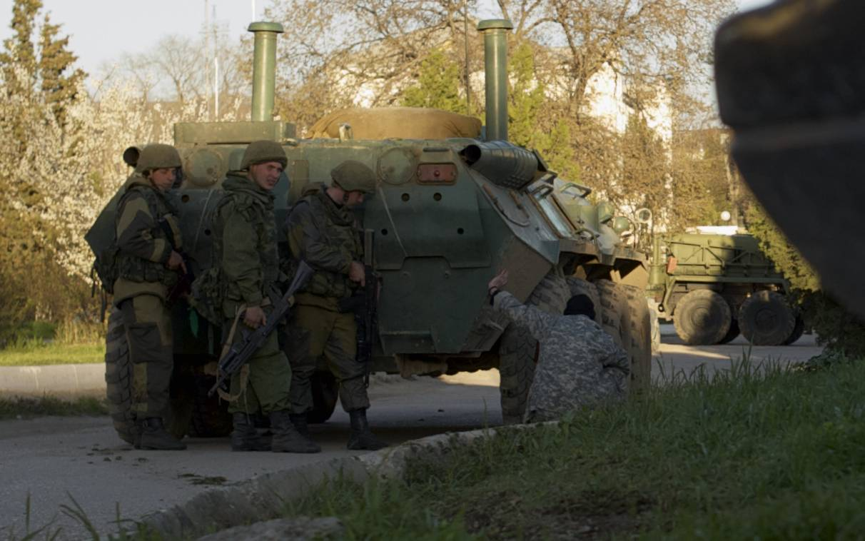 Russian soldiers take cover Saturday behind an APC outside the Ukrainian Belbek airbase outside Sevastopol, Crimea. Russian forces used at least four armored vehicles to break into the Belbek air base, seizing control of one of the last Ukrainian military outposts in Crimea.