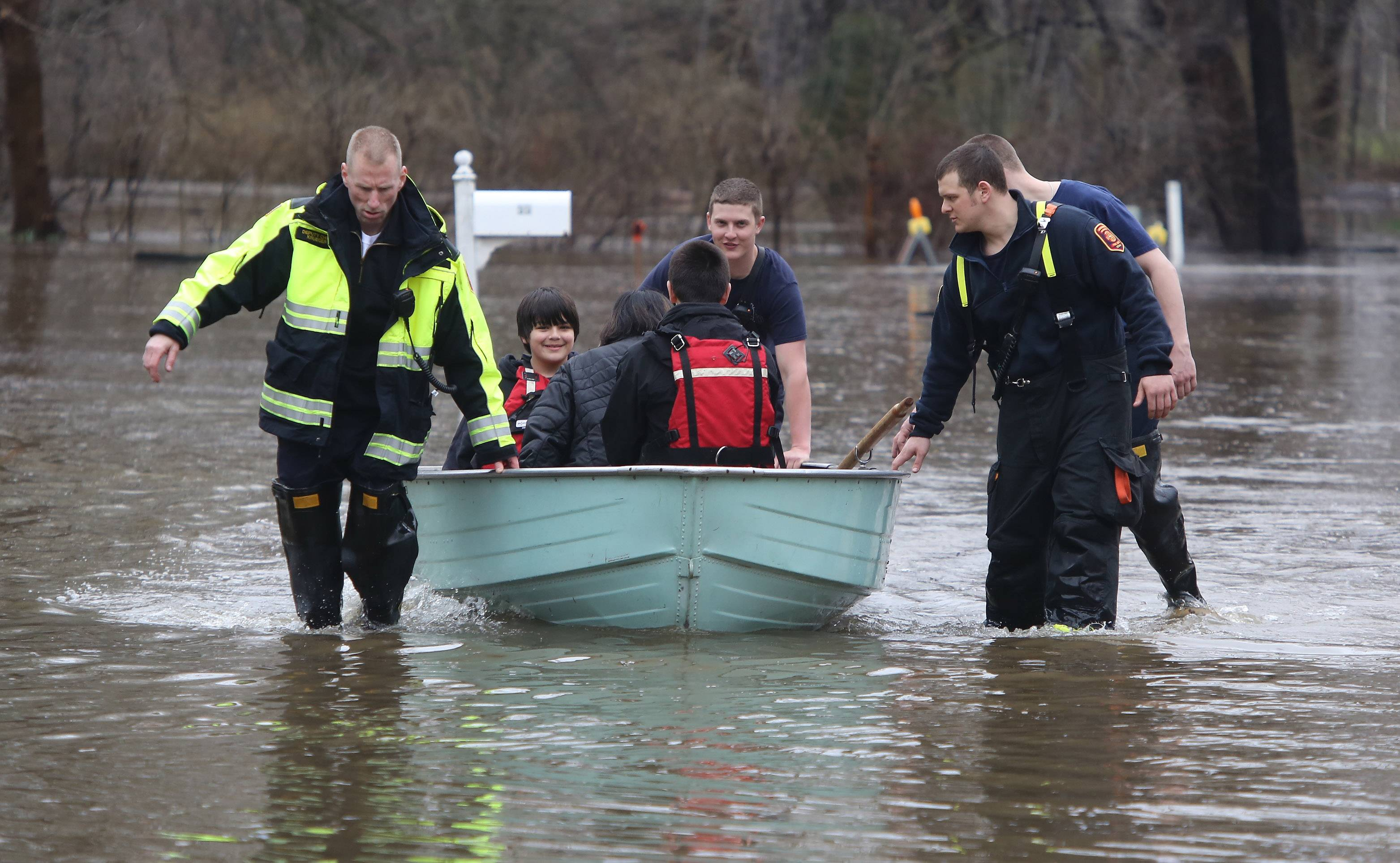 Lincolnshire-Riverwoods Fire Department firefighters assist residents as the leave their homes last year due to flooding of the Des Plaines River.