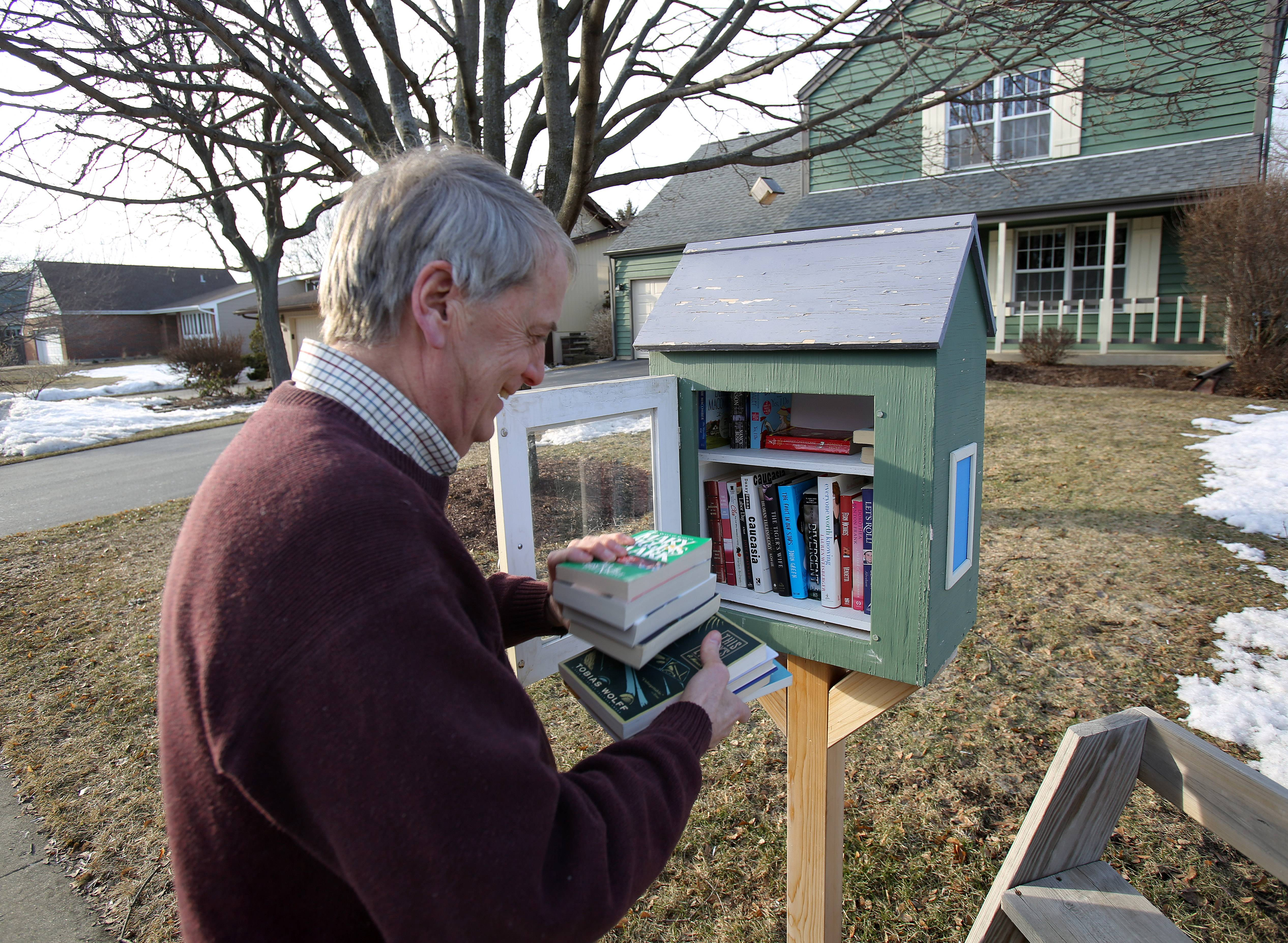 Brian Smith of Third Lake stocks the shelves of his Little Free Library. It sits in front of his house.