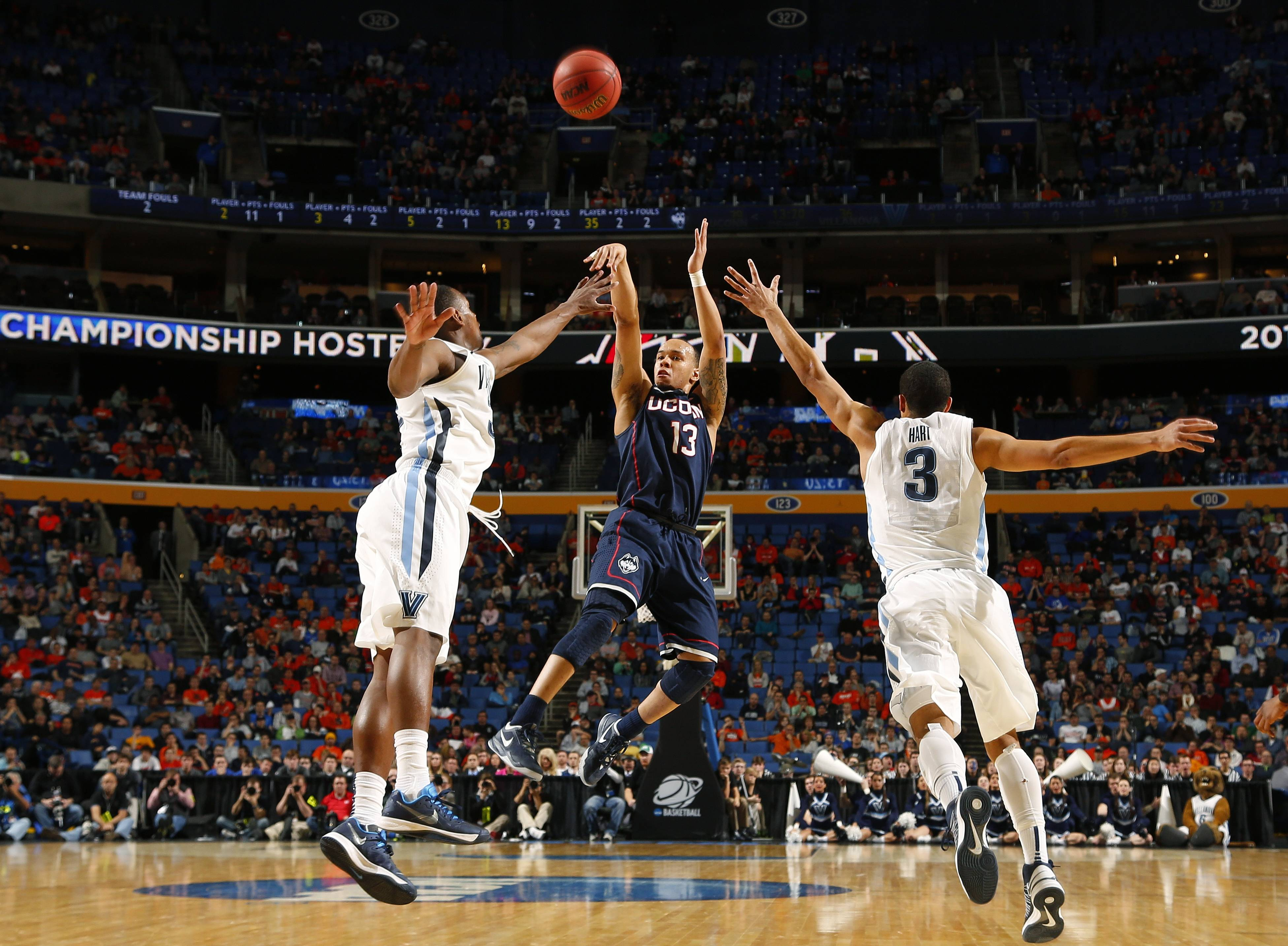 Villanova's Josh Hart (3) runs out to defend Connecticut's Shabazz Napier (13) during a third-round game in the NCAA men's college basketball tournament Saturday in Buffalo, N.Y. Napier scored 25 points in Connecticut's 77-65 win over Villanova.