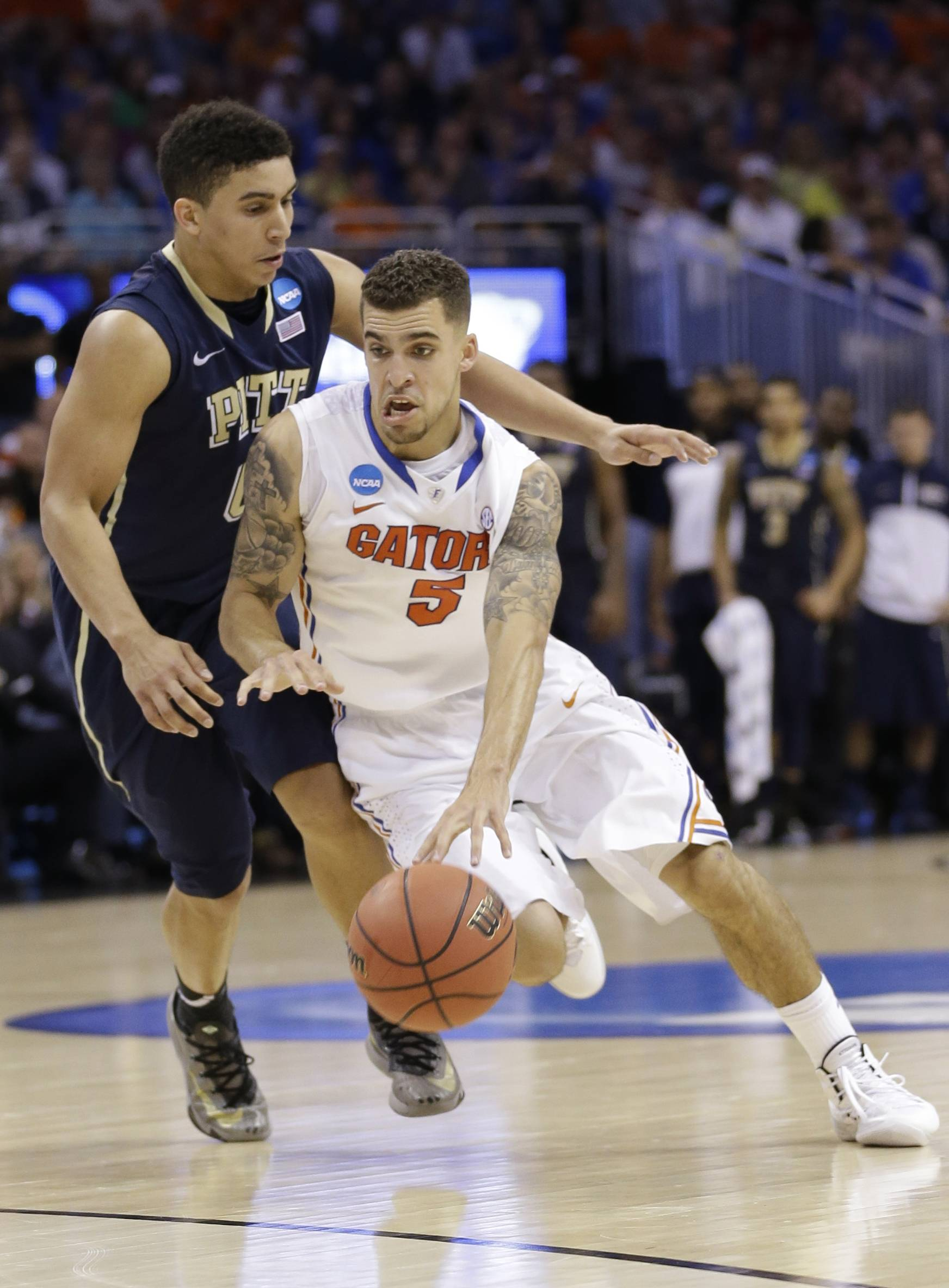 Florida guard Scottie Wilbekin (5) dribbles around Pittsburgh guard James Robinson (0) during a third-round game in the NCAA college basketball tournament Saturday in Orlando, Fla. Florida defeated Pittsburgh 61-45.