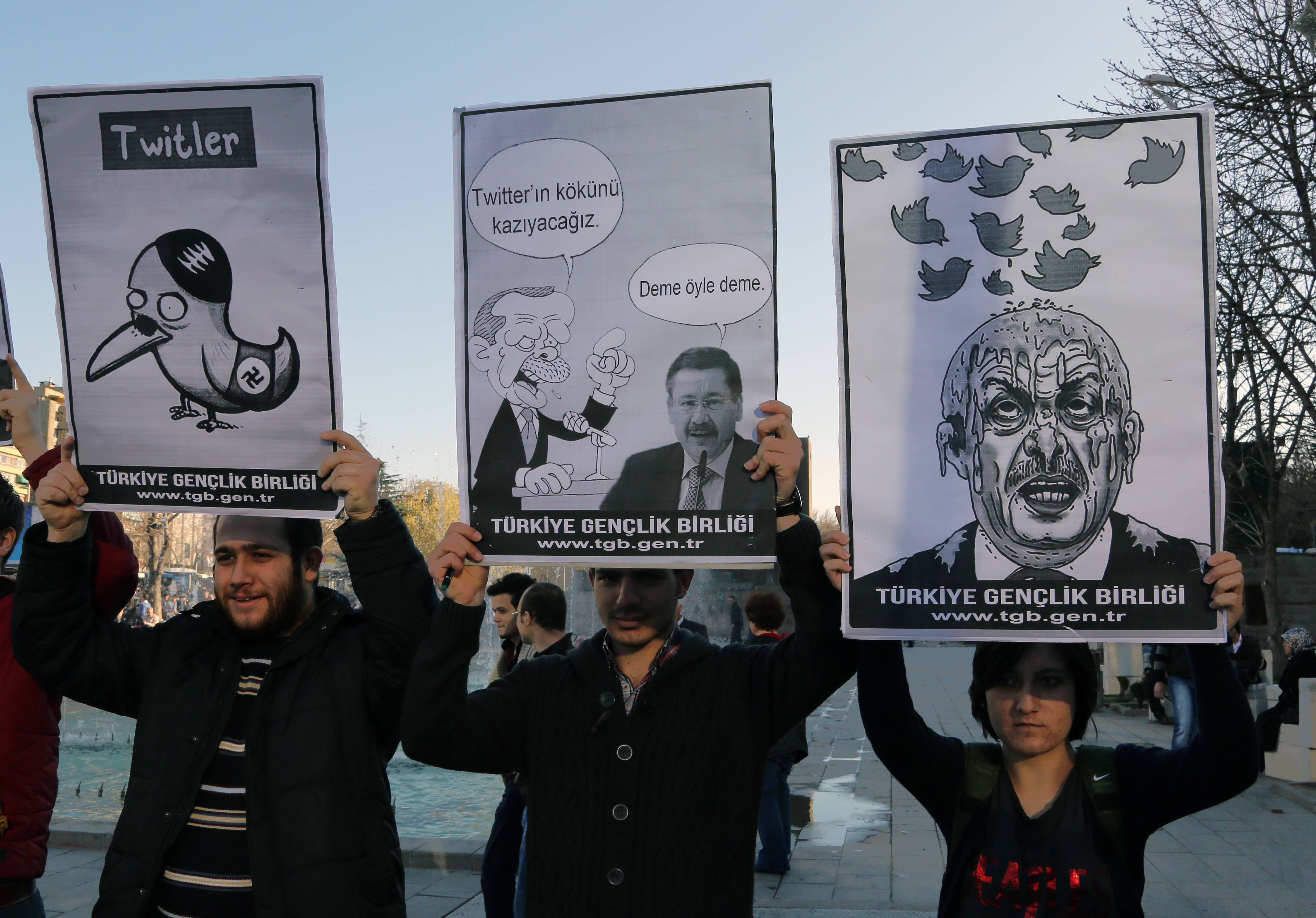 Members of the Turkish Youth Union hold cartoons Friday depicting Turkey's Prime Minister Recep Tayyip Erdogan during a protest against a ban on Twitter, in Ankara, Turkey.