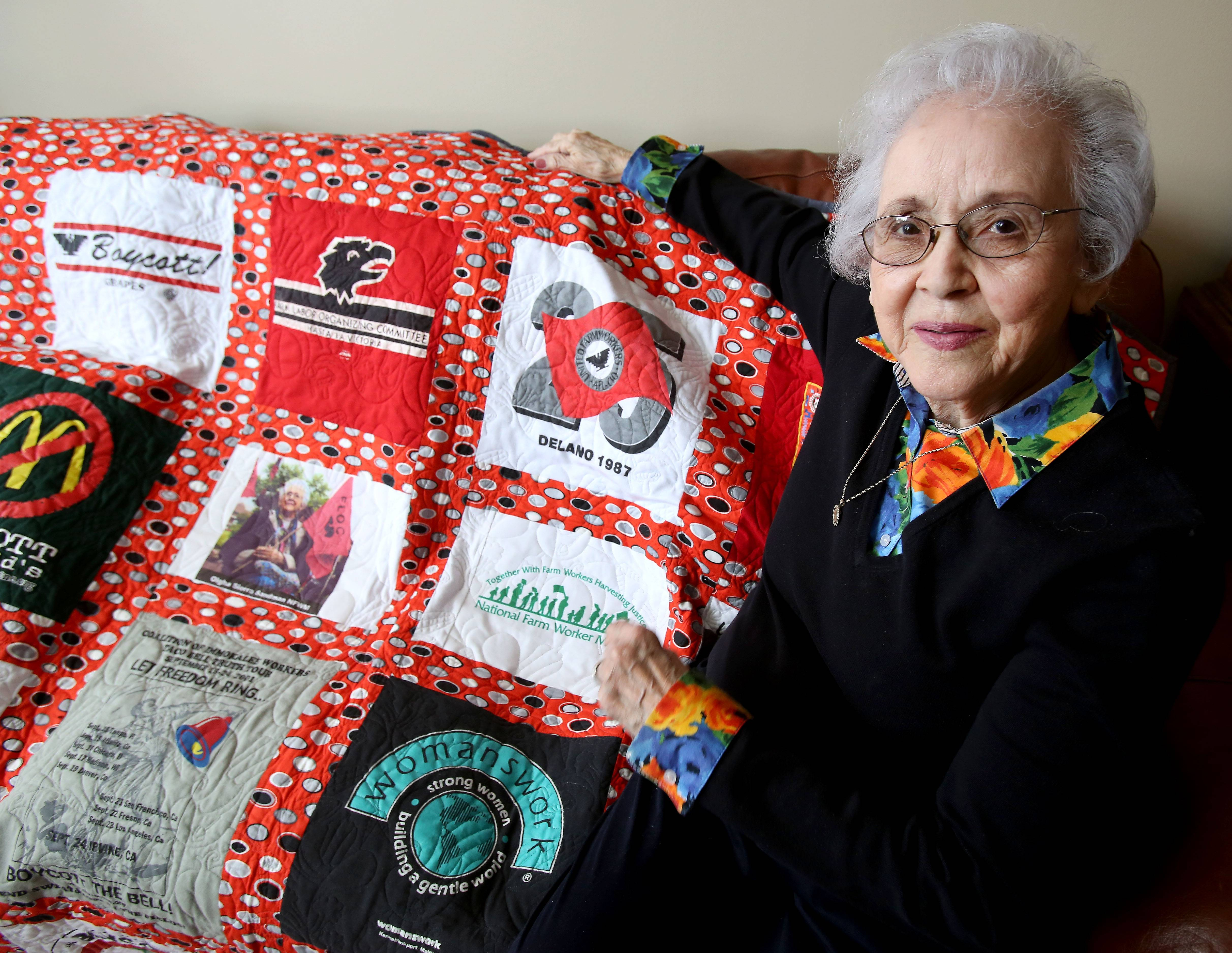 Olgha Sandman shows a quilt made of T-shirts she has relating to the migrant labor movement.