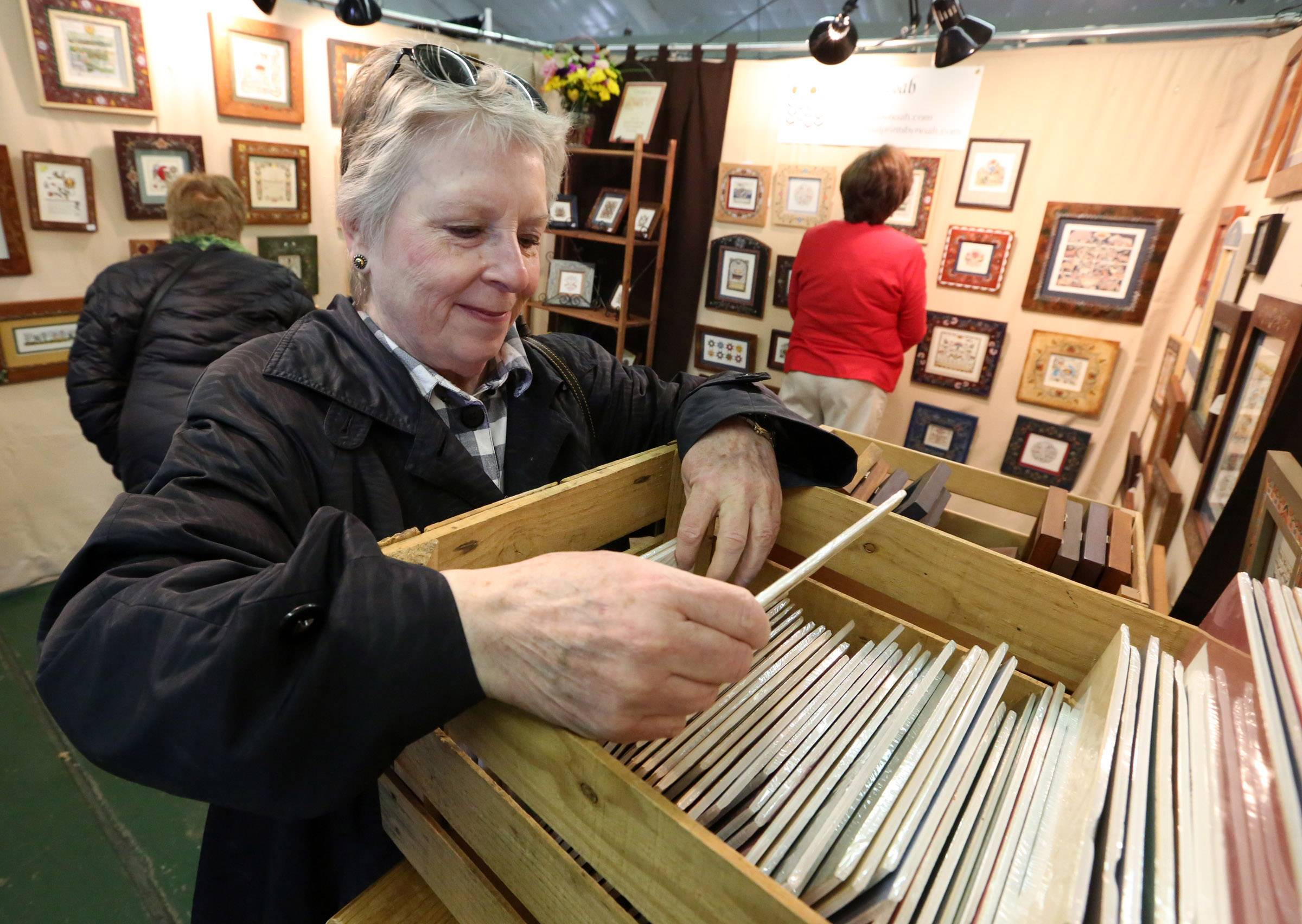 Deborah Boesch of Arlington Heights looks at art by Christine Noah-Cooper of Dayton, Ohio, during a Spring Country Folk Art Festival at Kane County Fairgrounds on Saturday in St. Charles.