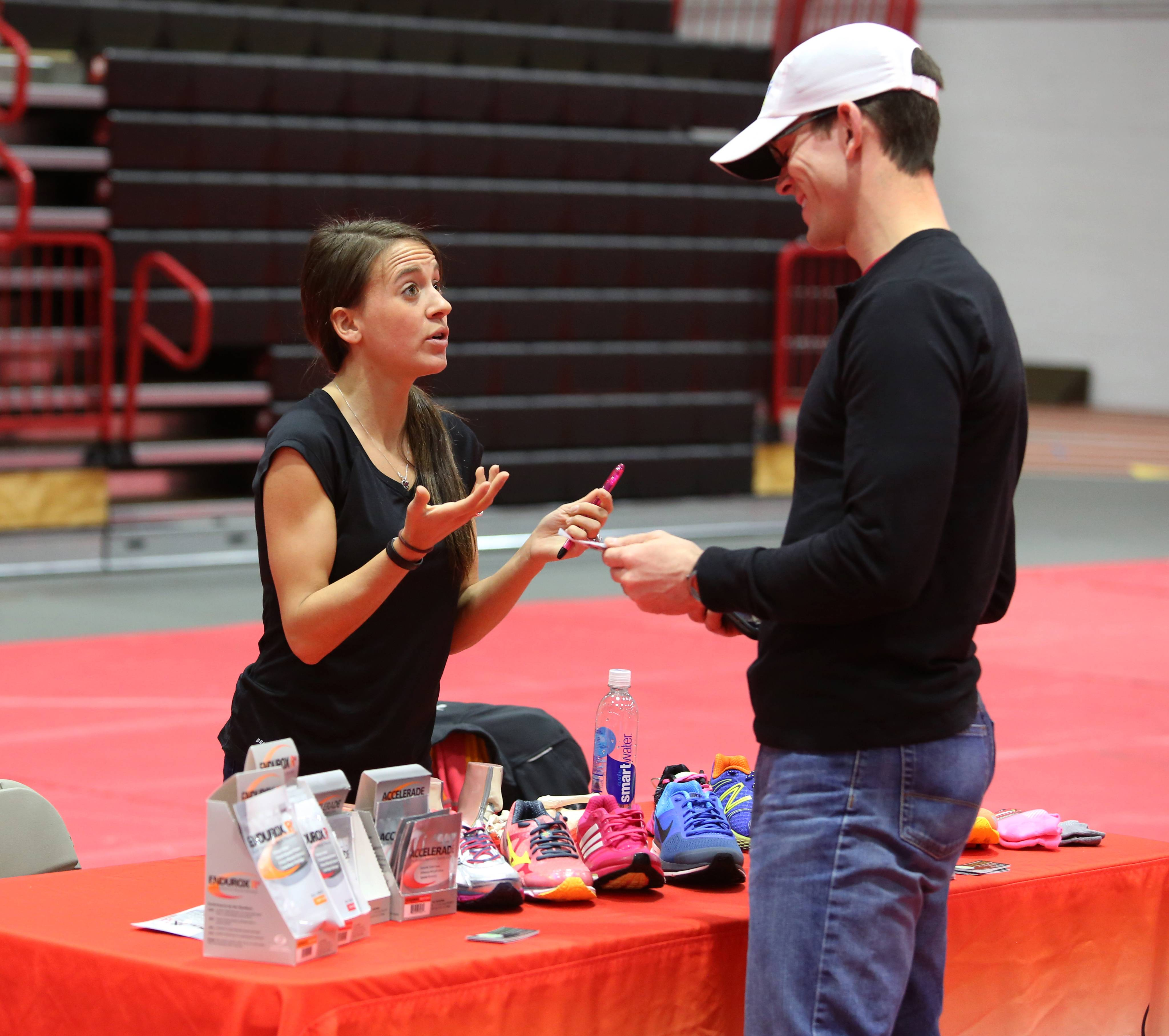 Marisa Hird of Naperville Running talks with running coach Seth Kopf of Lake in the Hills during a runners symposium hosted by Athletico at North Central College.