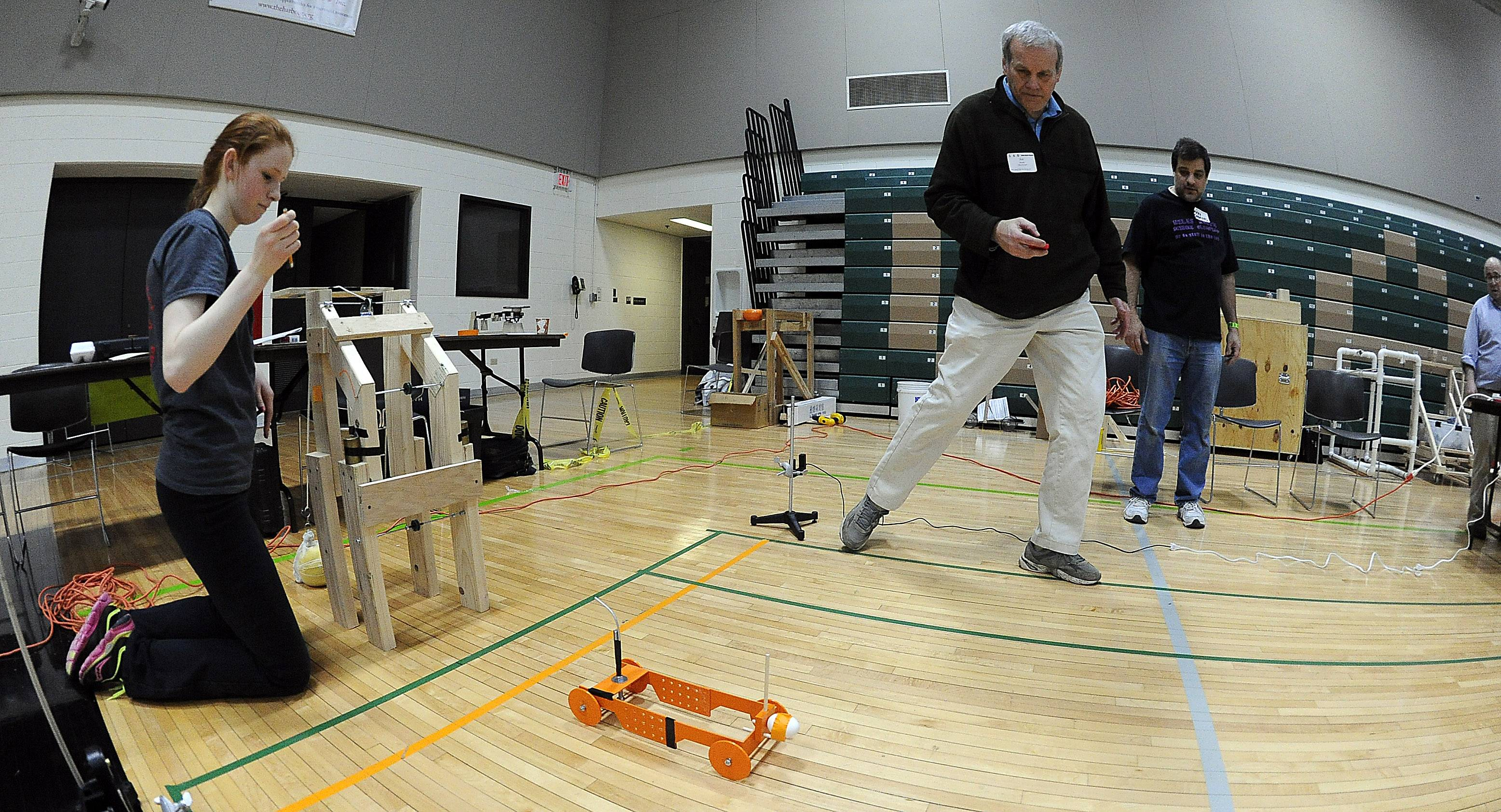 Kiera Gavin of Palatine High School demonstrates her science project to timer Joe Hanafee in the Scrambler event Saturday at the Science Olympiad at Oakton Community College in Des Plaines. Winners in the regional event will move on to state.