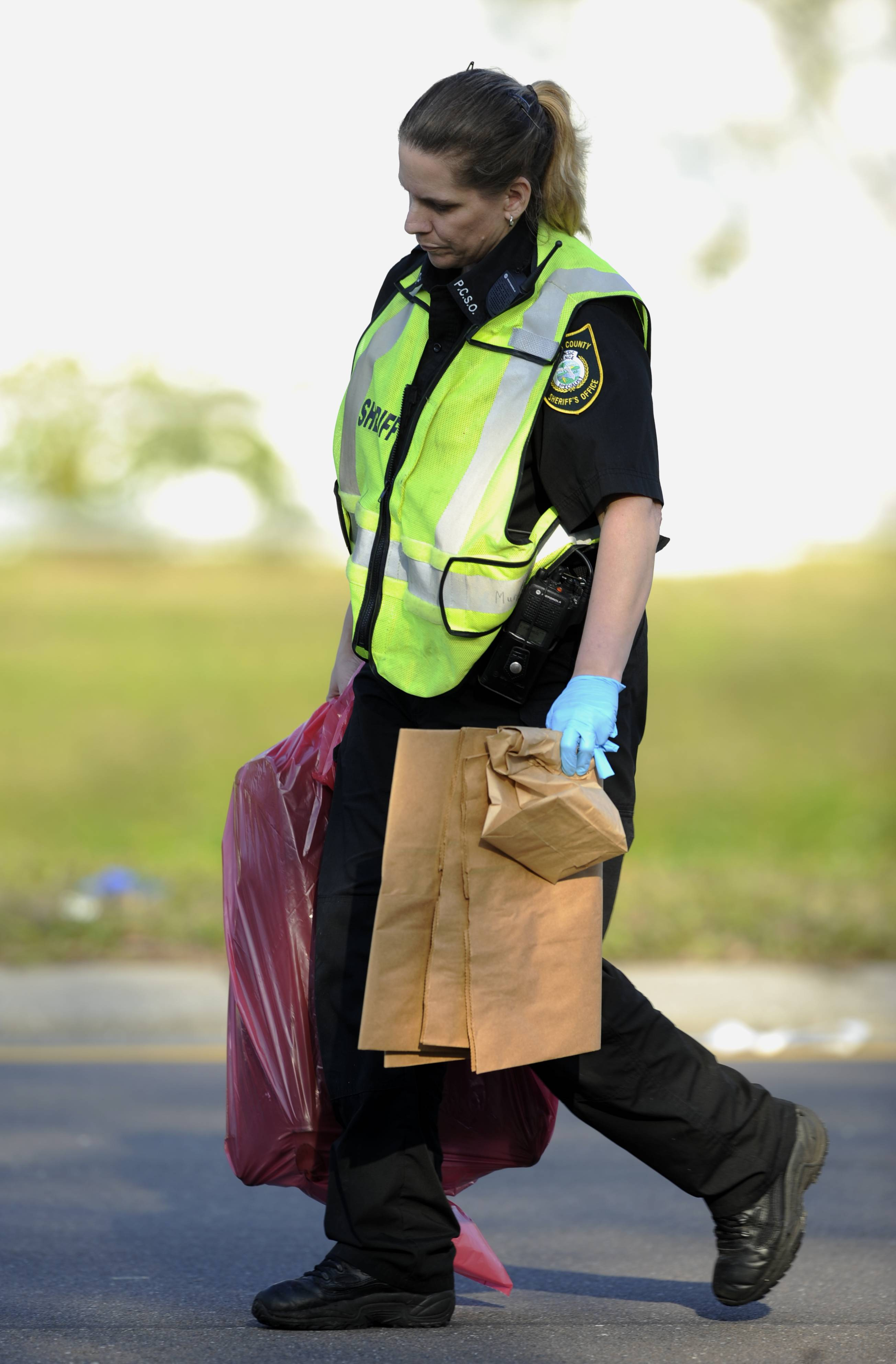A crime scene technician with Pinellas County Sheriff's Office carries items from the scene of a small passenger plane which crashed early Saturday near Clearwater, Fla.