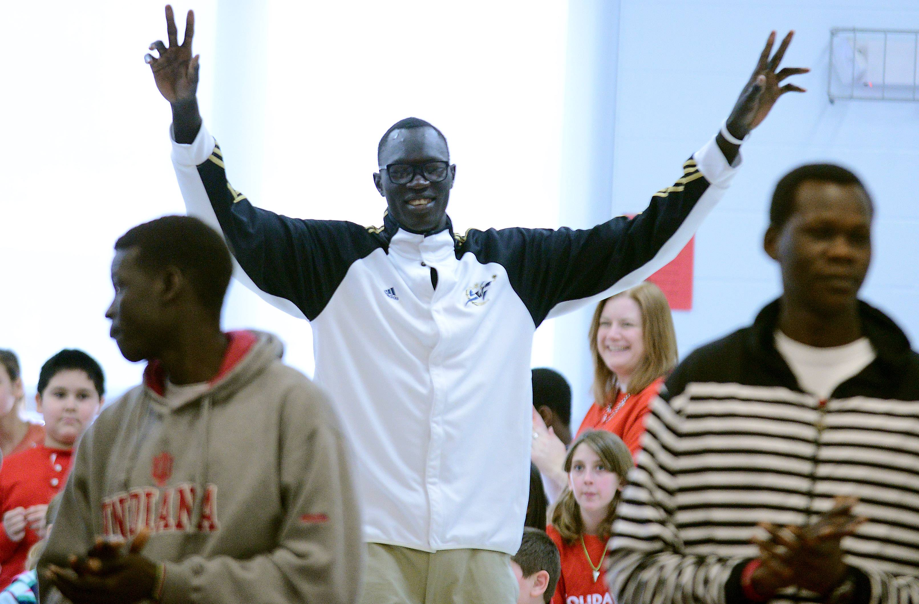 Above, Makur Puou joins his teammates onstage as the Mooseheart Class 1A state champion basketball team is honored in a ceremony for state-qualifying athletes in fall and winter sports Friday at the school.