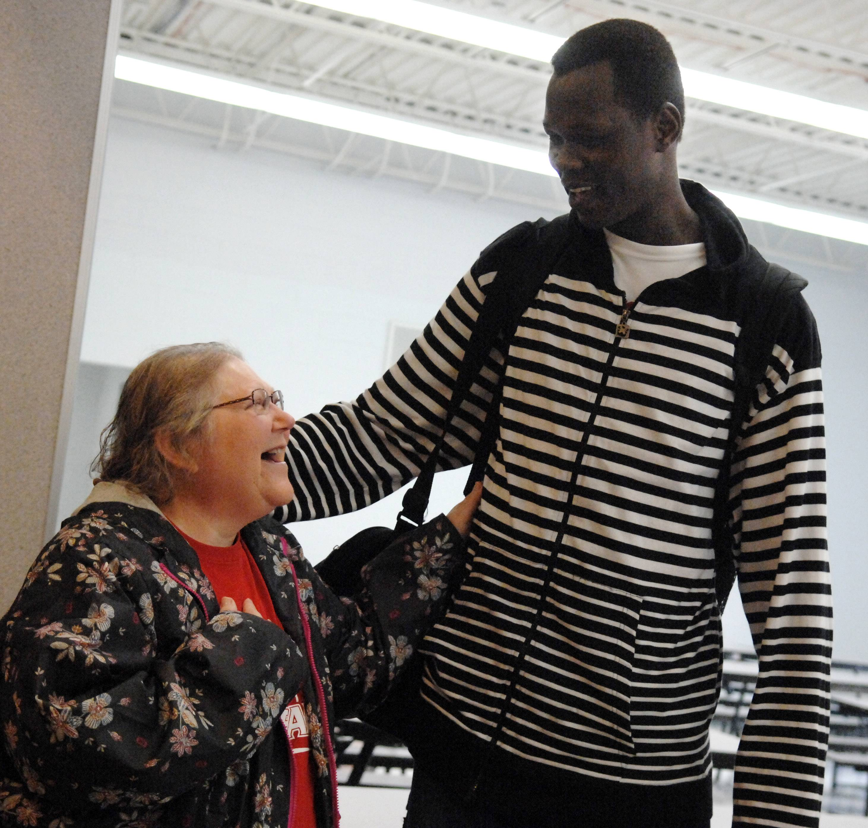 Basketball player Akim Nyang gets a hug from athletic secretary Mary Beth Hake following a ceremony honoring the basketball team Friday at Mooseheart. The ceremony also honored other athletes, including the school's first state qualifying wrestler and a cross-country runner who finished fourth at state.