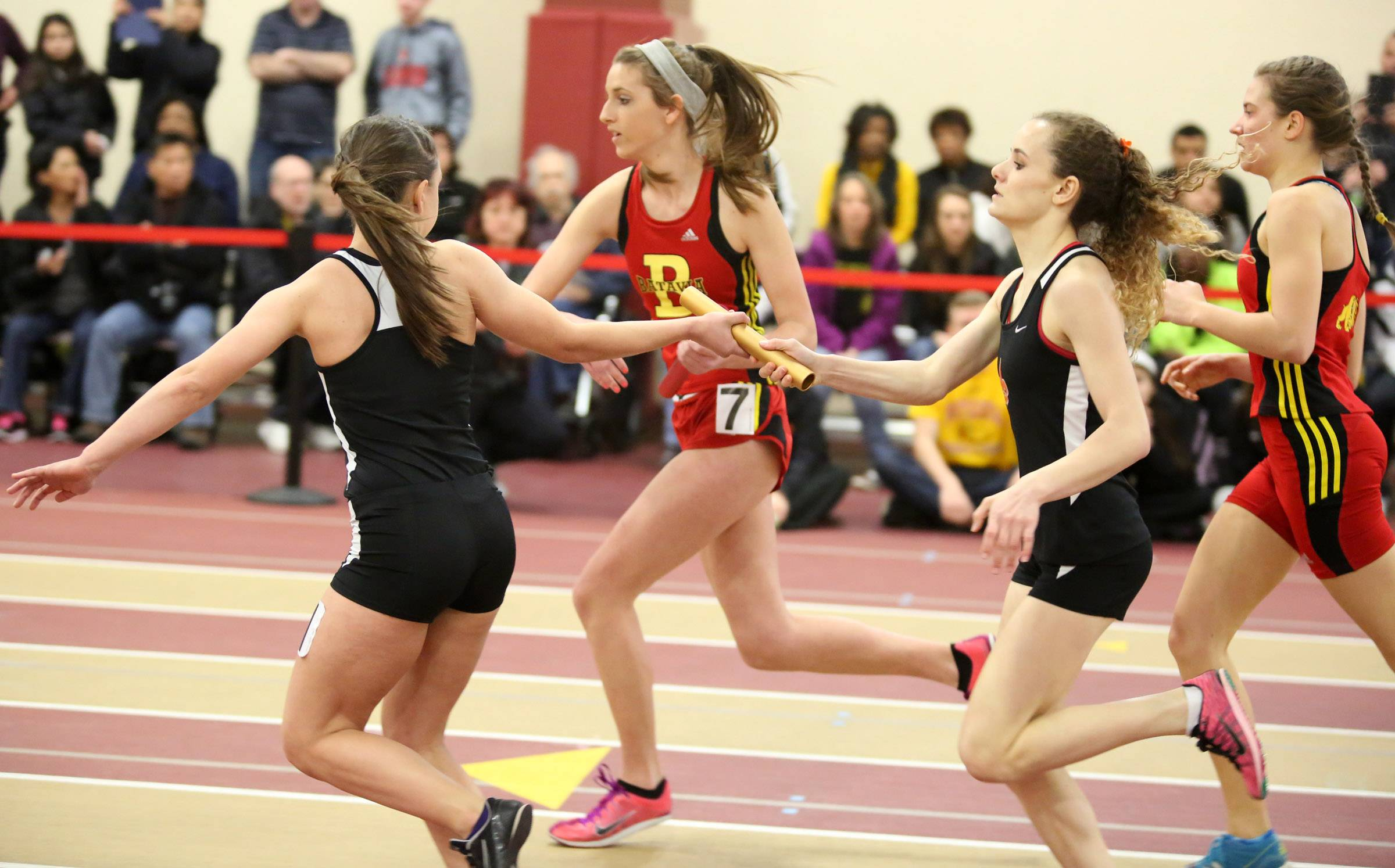 St. Charles East Anastasia Honea, right, hands the baton to Corrin Adams for the last leg of 3,200 relay at the Upstate Eight Conference indoor track meet on Saturday at Batavia.