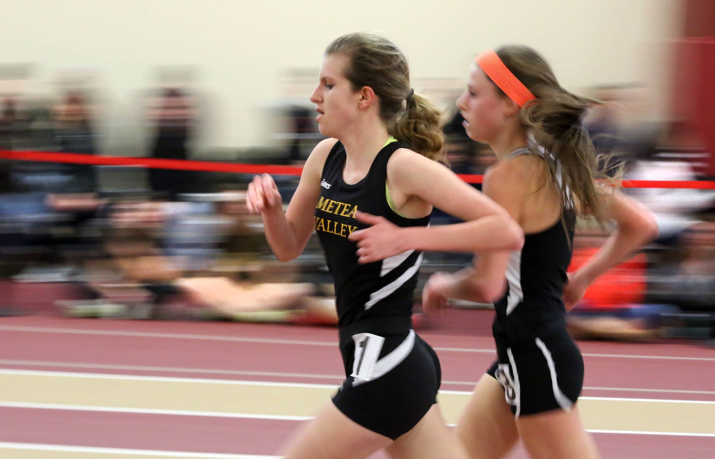 Meta Valley Kendall Cast and St. Charles East Torree Scull running neck to neck in the 3200 meter at an Upstate Eight Conference indoor track meet on Saturday at Batavia.