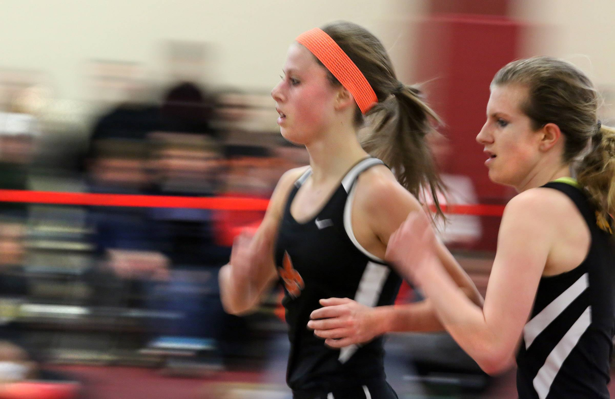 St. Charles East Torree Scull, left, and Meta Valley Kendall Cast running neck to neck in the 3200 meter at an Upstate Eight Conference indoor track meet on Saturday at Batavia