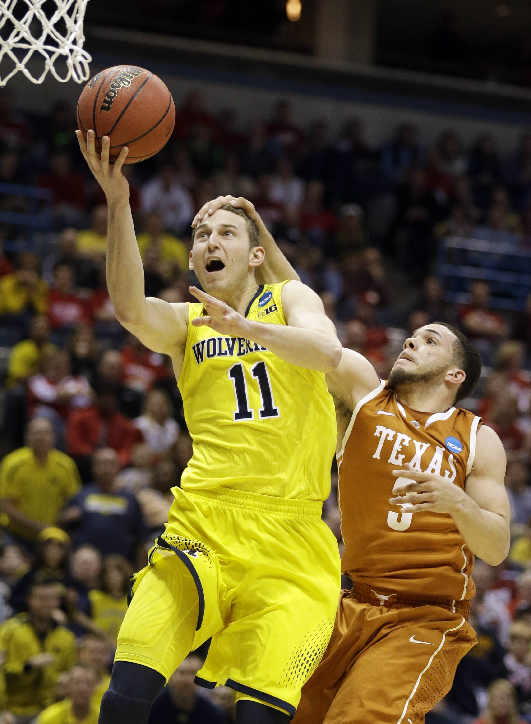 Michigan guard Nik Stauskas (11) is fouled by Texas guard Javan Felix (3) during a third-round game of the NCAA college basketball tournament Saturday in Milwaukee. Michigan beat Texas 79-65.