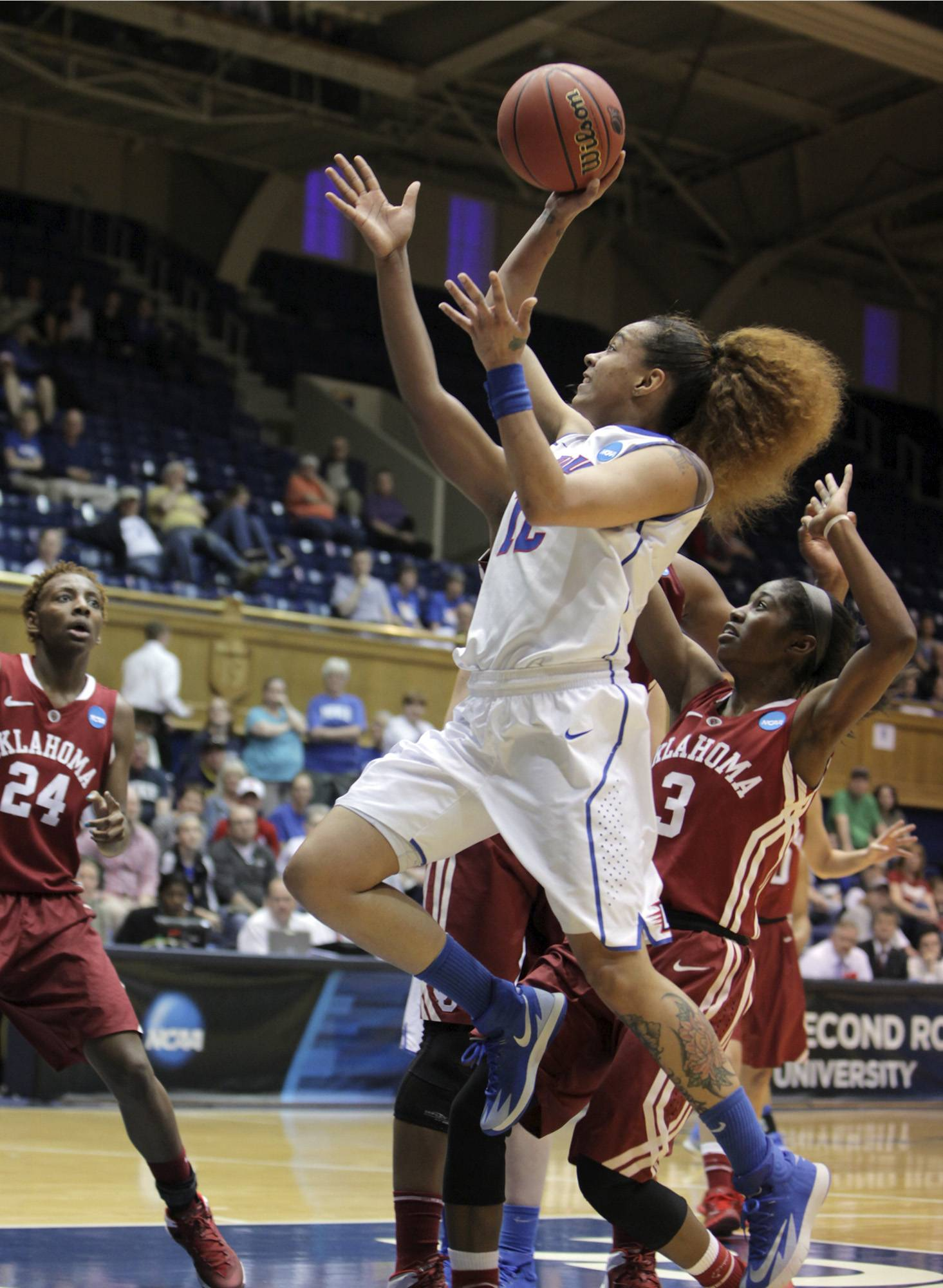 DePaul's Brittany Hrynko drives to the basket between Oklahoma's Aaryn Ellenberg (3) and Sharane Campbell (24) during their first-round game in the NCAA women's college basketball tournament Saturday in Durham, N.C. DePaul won 104-100.