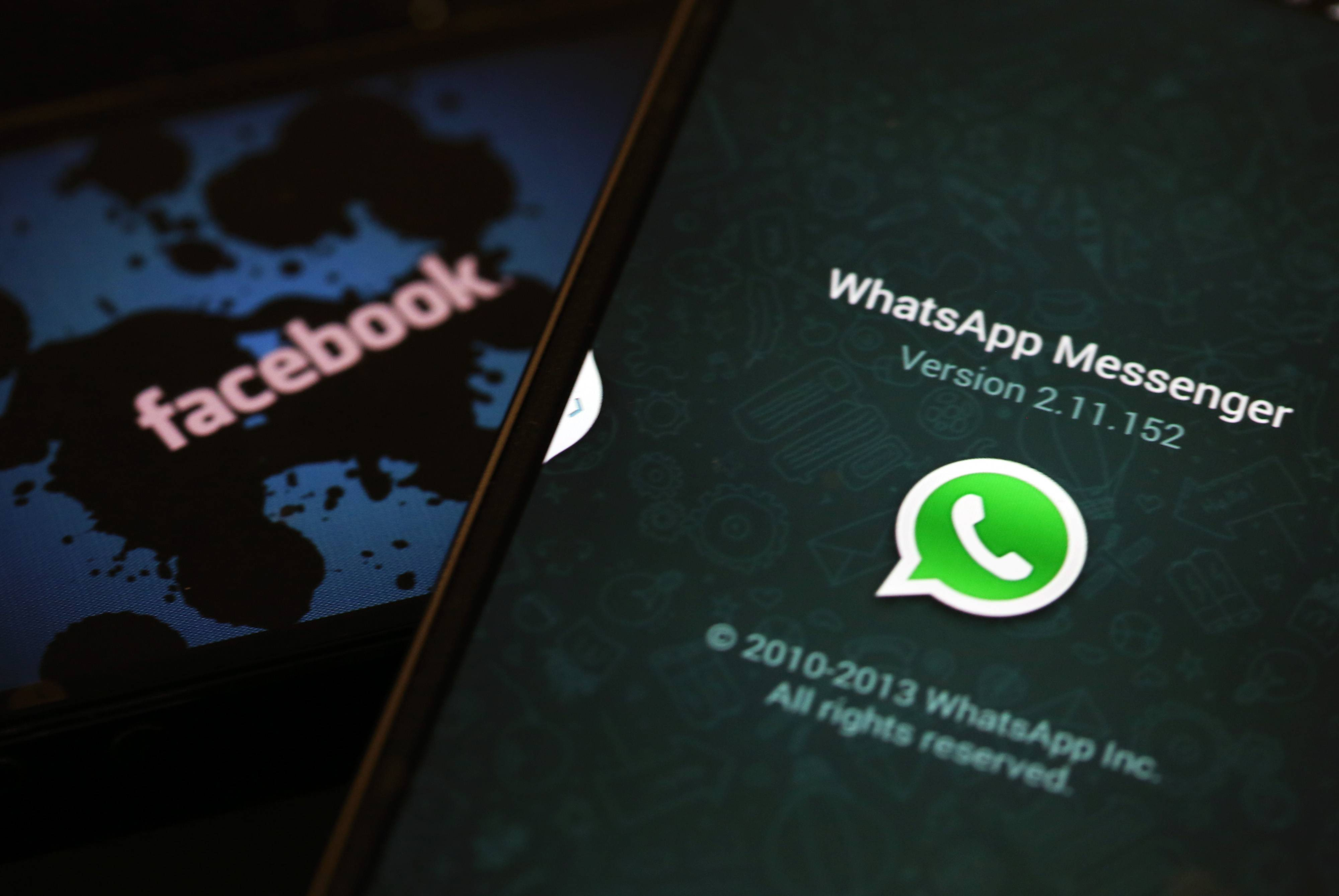 The WhatsApp Inc. mobile-messaging application WhatsApp and a Facebook Inc. logo are displayed on an the screens of mobile handsets.