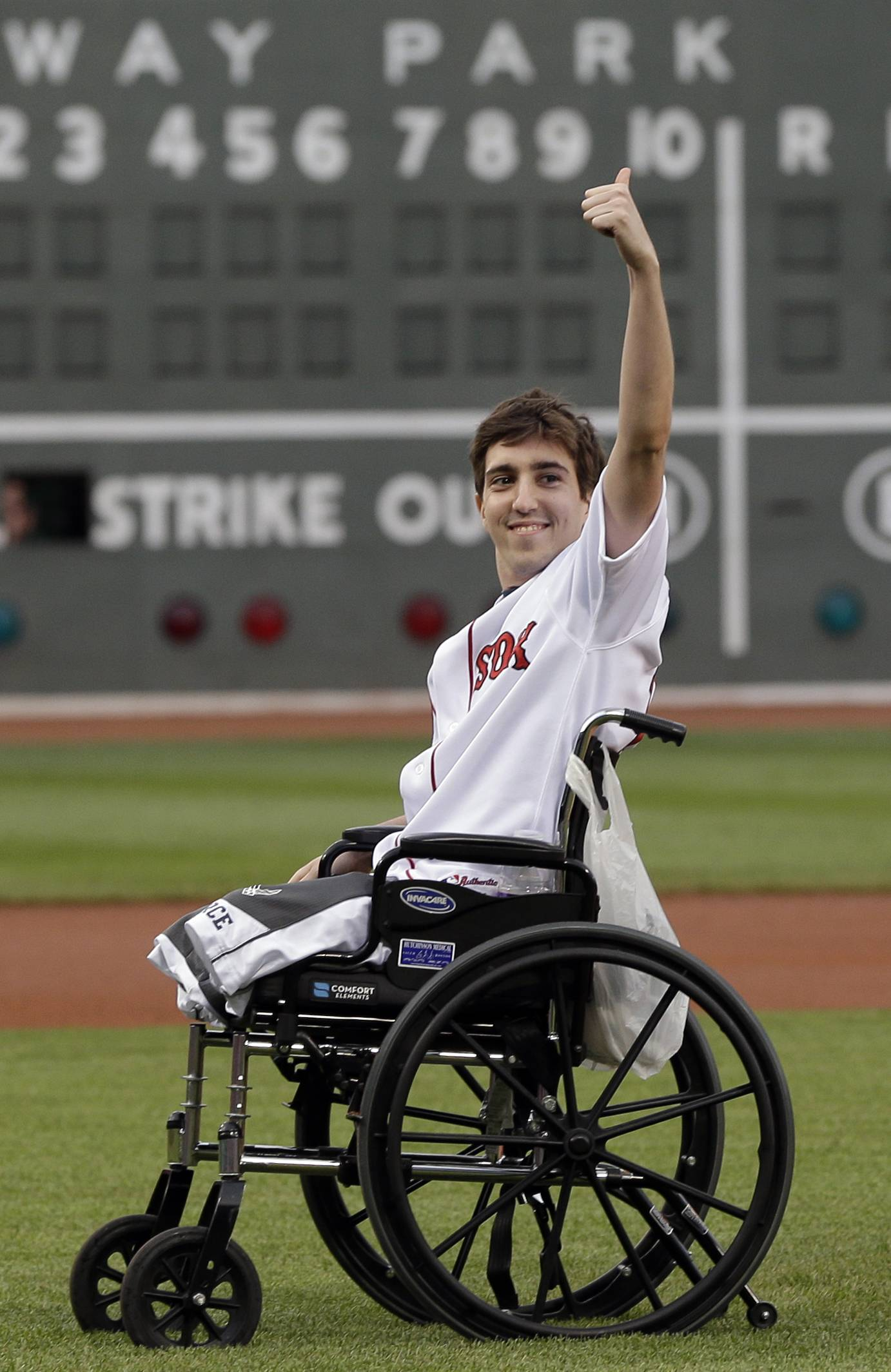 Boston Marathon bombing survivor Jeff Bauman acknowledges cheering fans before throwing out a ceremonial first pitch at Fenway Park May 28, 2013. Bauman, who lost both legs in the bombings and then helped authorities identify the suspects, is engaged and an expectant father. He and his fiancé, Erin Hurley, say the baby is due July 14.