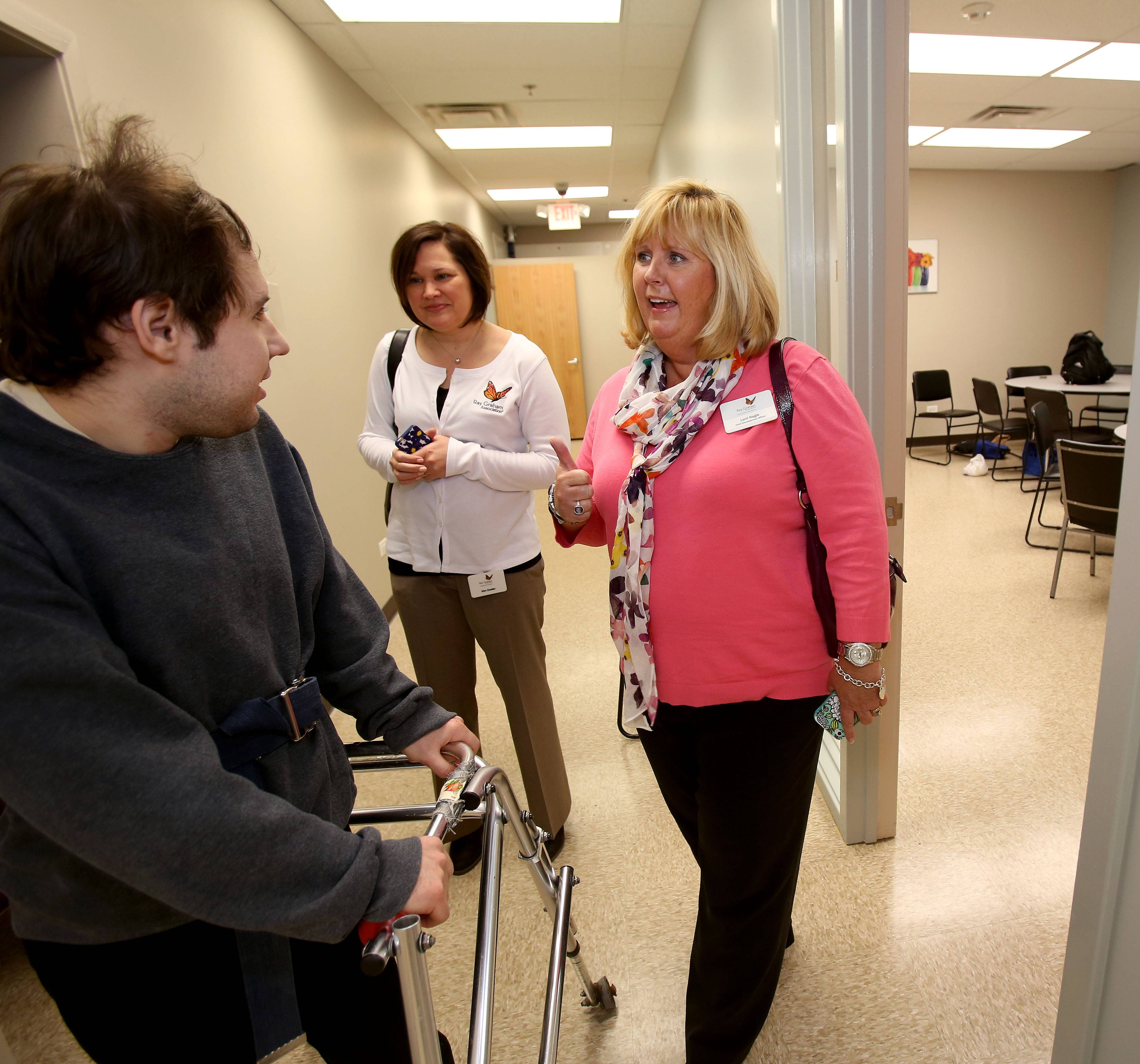Richard Changlon, left, of Bensenville, chats with Ray Graham Association President and Chief Executive Officer Kim Zoeller and Chief Development Officer Lori Nagle during the grand reopening of the association's community learning center Friday in Lombard.