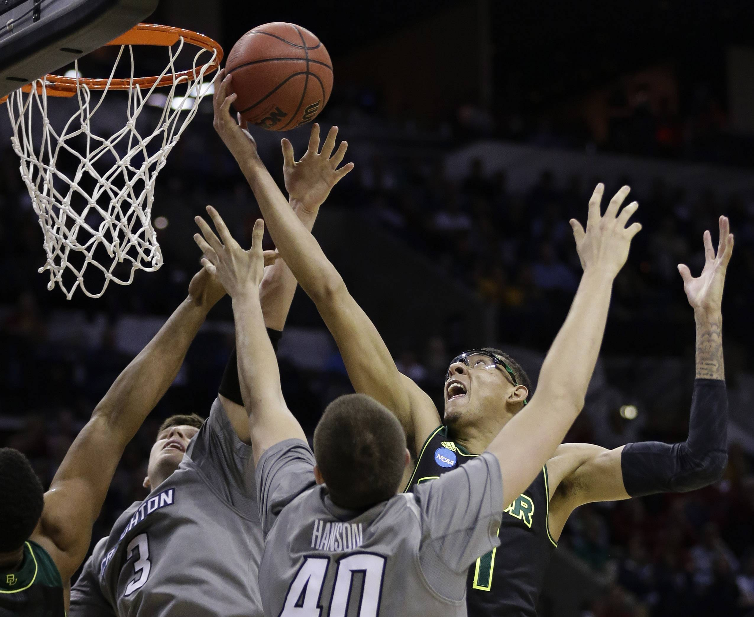 Baylor's Isaiah Austin, right, reaches over Creighton's Doug McDermott (3) and Zach Hanson (40) for a rebound during the first half of a third-round game in the NCAA college basketball tournament Sunday, March 23, 2014, in San Antonio.