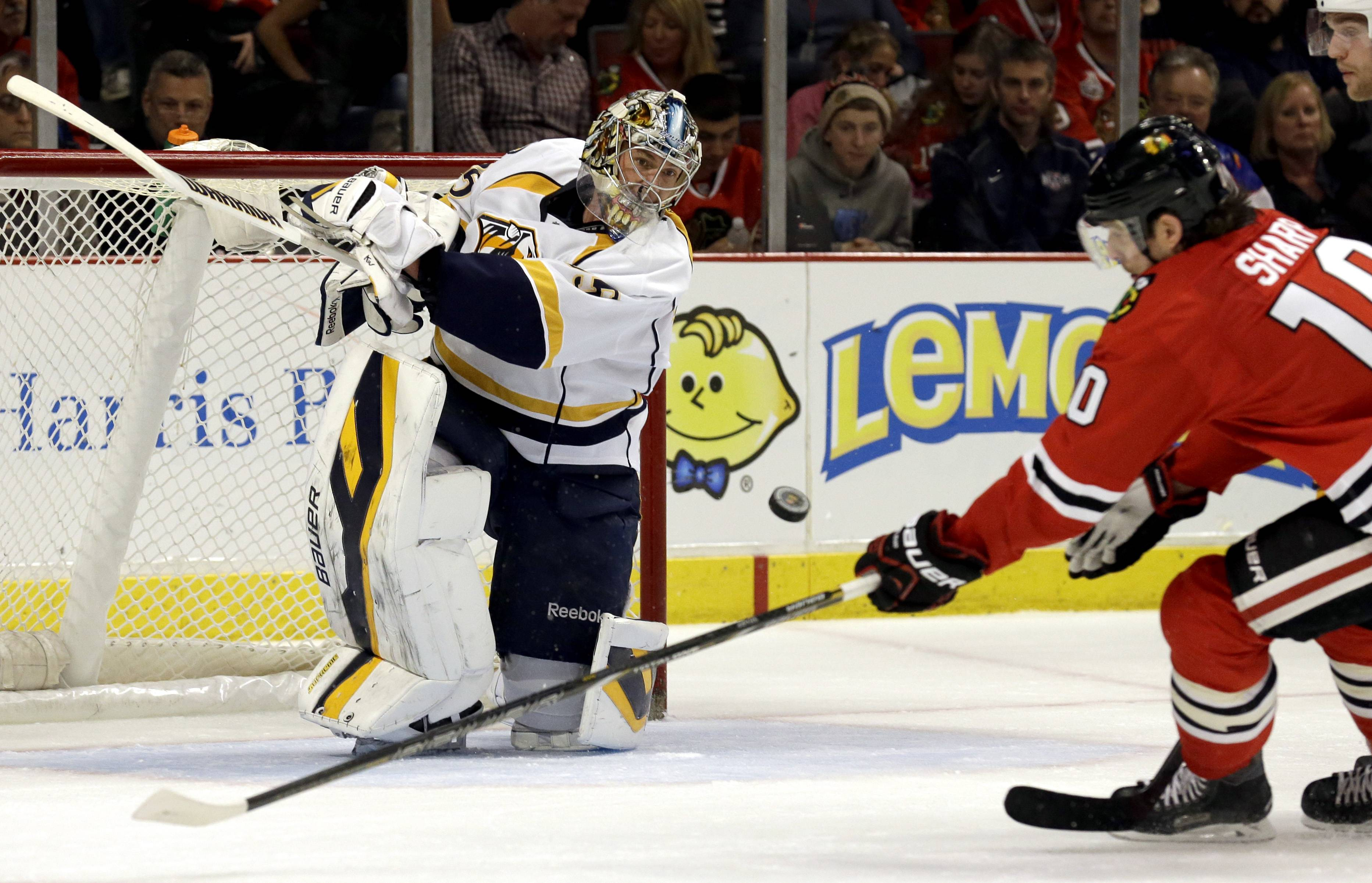 Nashville Predators goalie Pekka Rinne (35), left, blocks a shot by Chicago Blackhawks' Patrick Sharp (10) during the second period of an NHL hockey game in Chicago, Sunday, March 23, 2014.