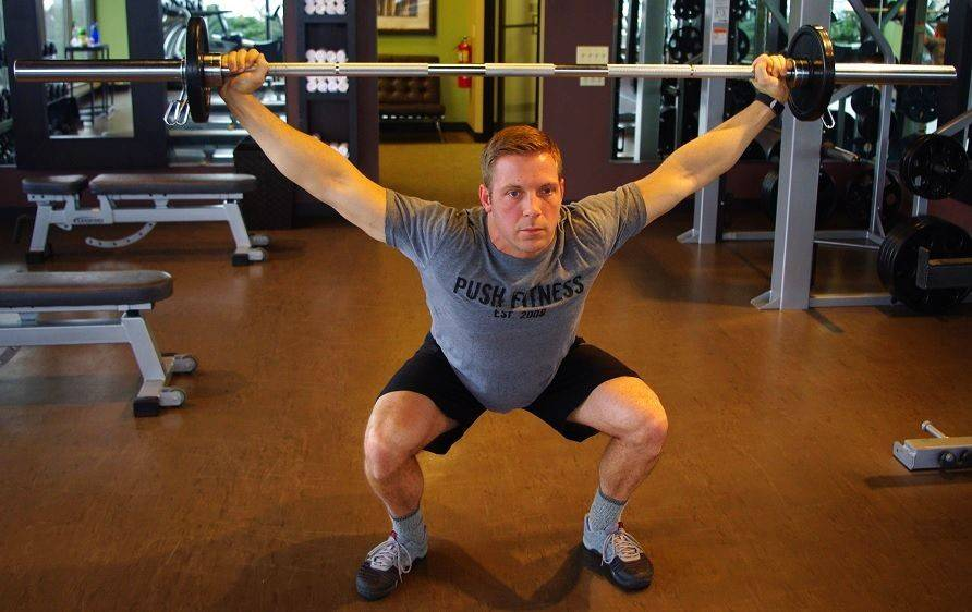 With the bar overhead, this exercise becomes a total-body exercise and requires much more balance, stability and flexibility than a typical squat.