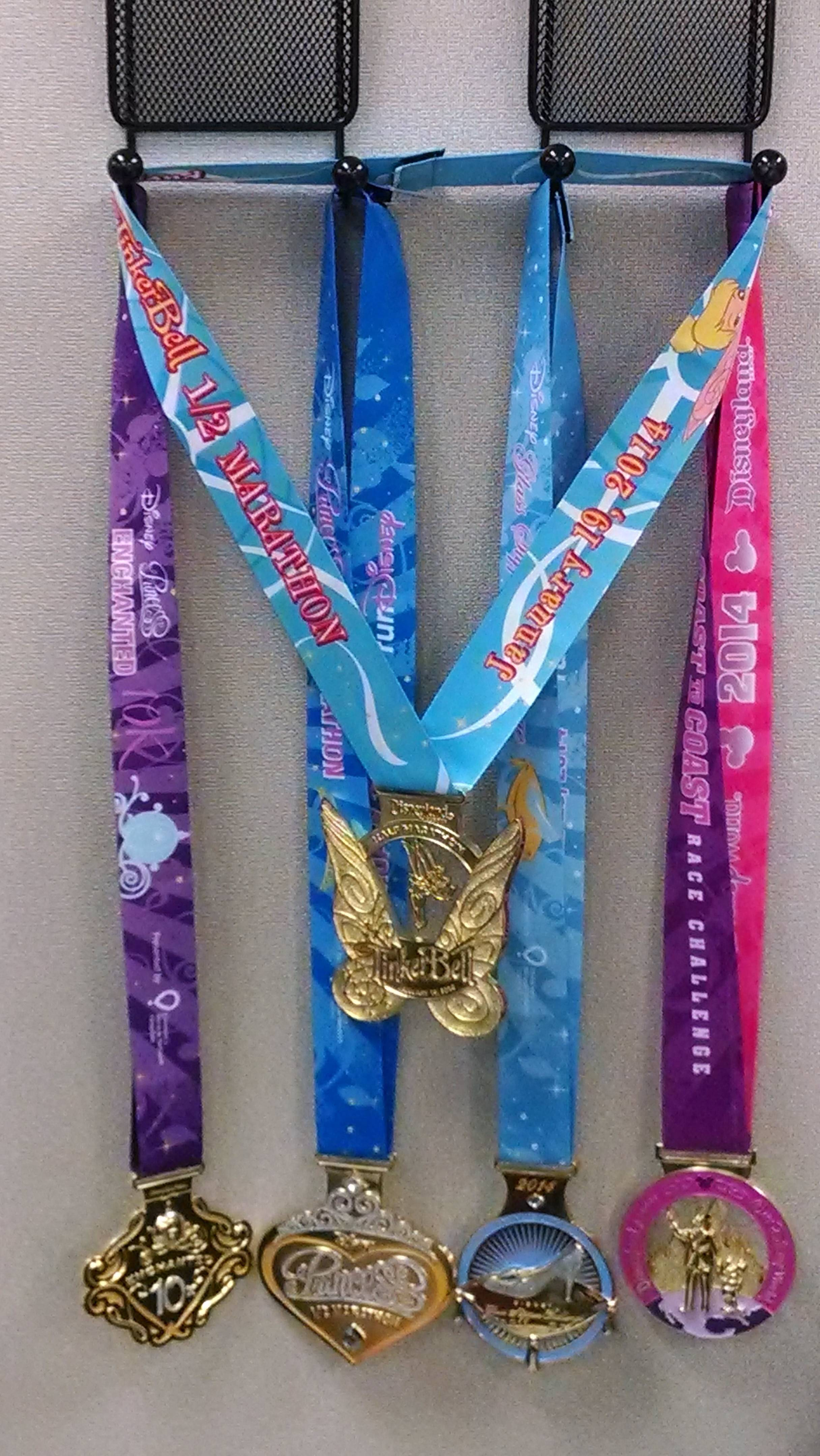 The Horvaths show off five of the elaborate race medals they've earned at runDisney races.