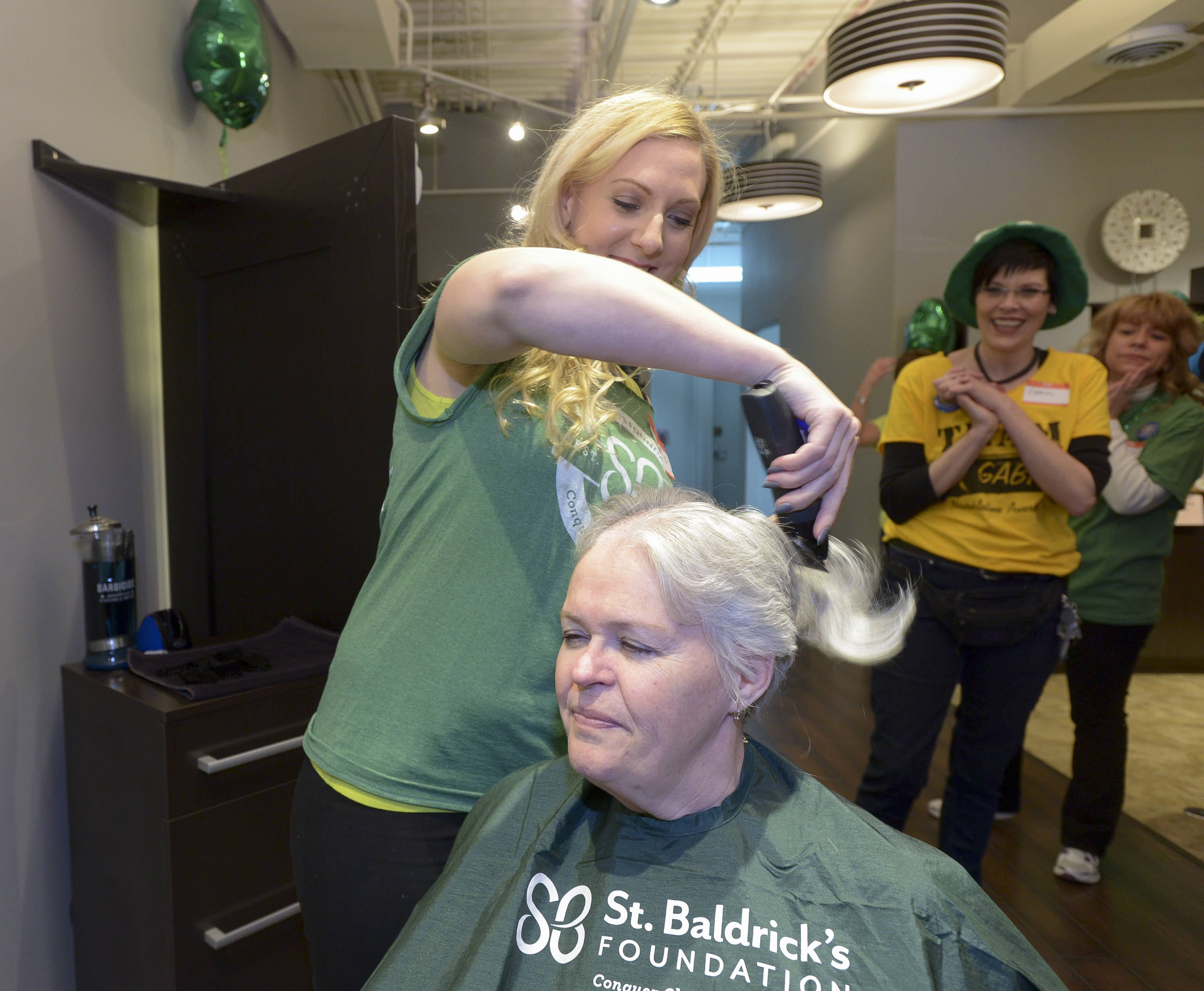 Maureen Maguire of Cary has her head shaved by Devin Dalakouras while participating in the St. Baldrick's head shaving event Sunday at Rue 62 Salon/1st Place Sports Bar & Grill in Hoffman Estates. Maguire raised $1,270 for the St. Baldrick's Foundation.