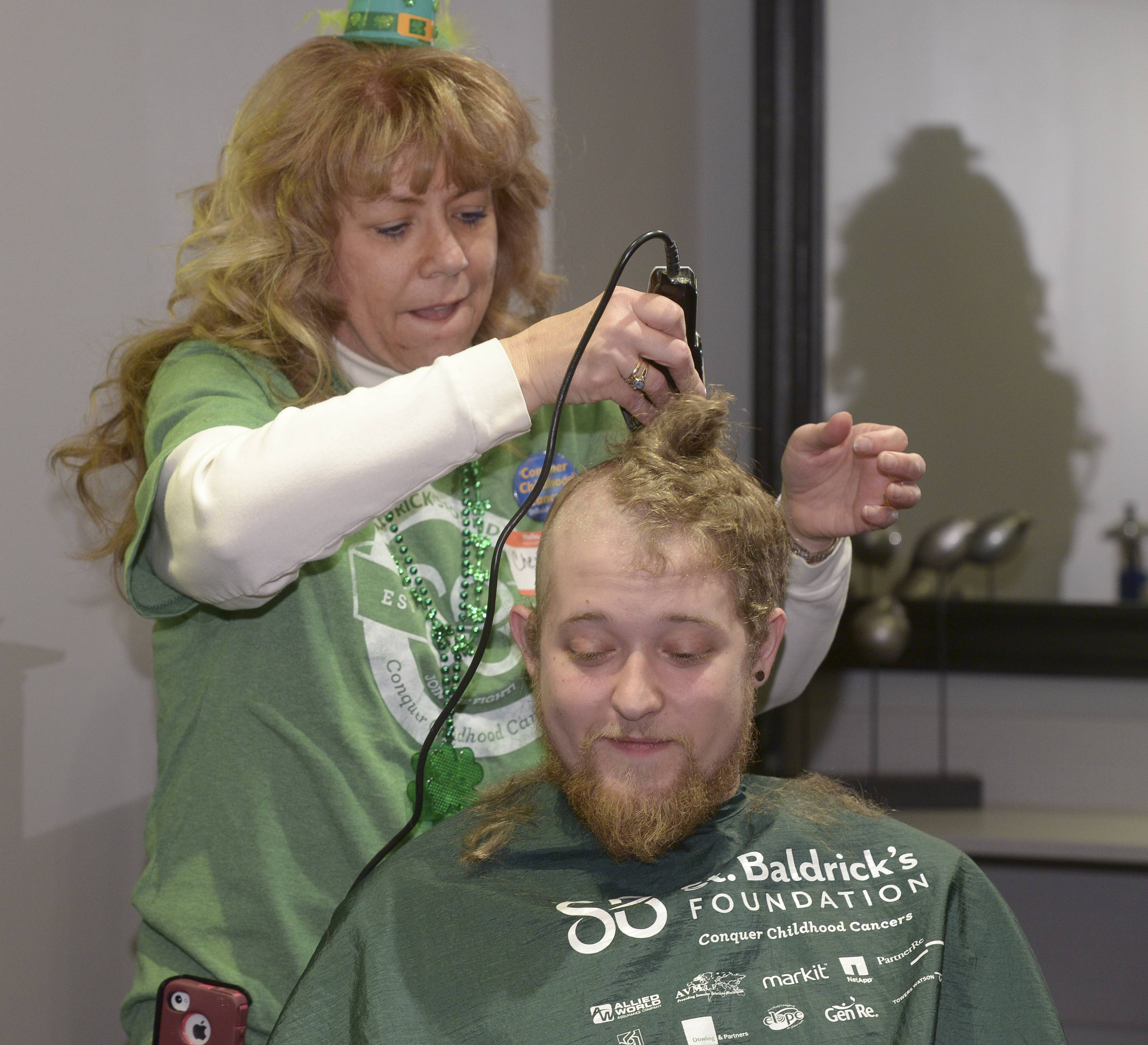 "Matt Popovich of Algonquin has his head shaved by Cheryl Lyons while participating in Sunday's the St. Baldrick's fundraiser at Rue 62 Salon/1st Place Sports Bar & Grill in Hoffman Estates. Popovich said he heard about the event on the radio and thought it was a win-win. ""If I was going to get a haircut anyway (I) might as well make it worth something,"" he said."