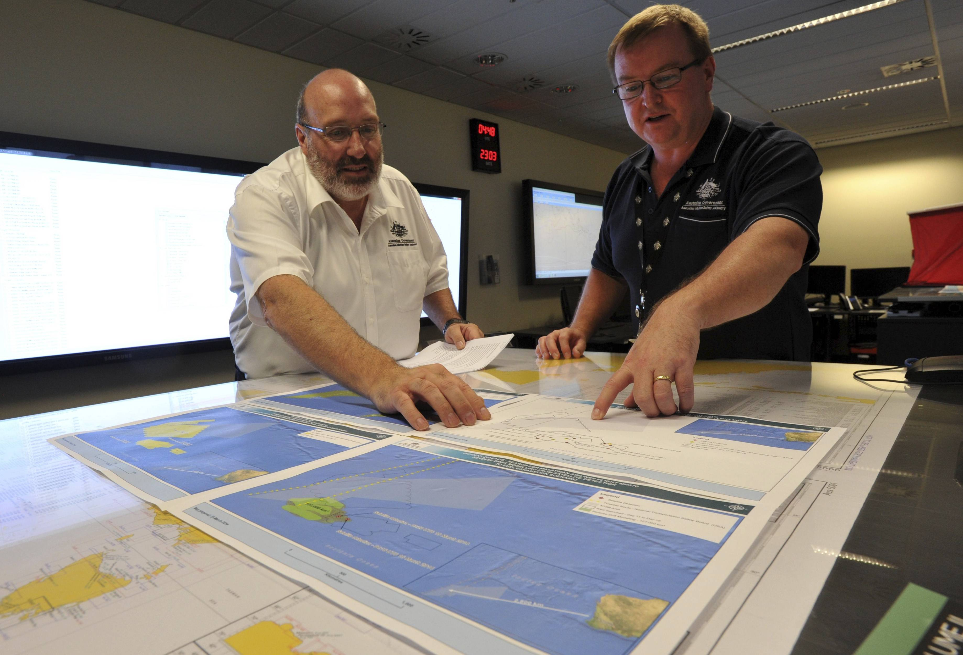 Mike Barton, rescue coordination chief, left, looks over the maps of the Indian Ocean with Alan Lloyd, manager of search and rescue operations at the Australian Maritime Safety Authority's rescue coordination center in Canberra Sunday.