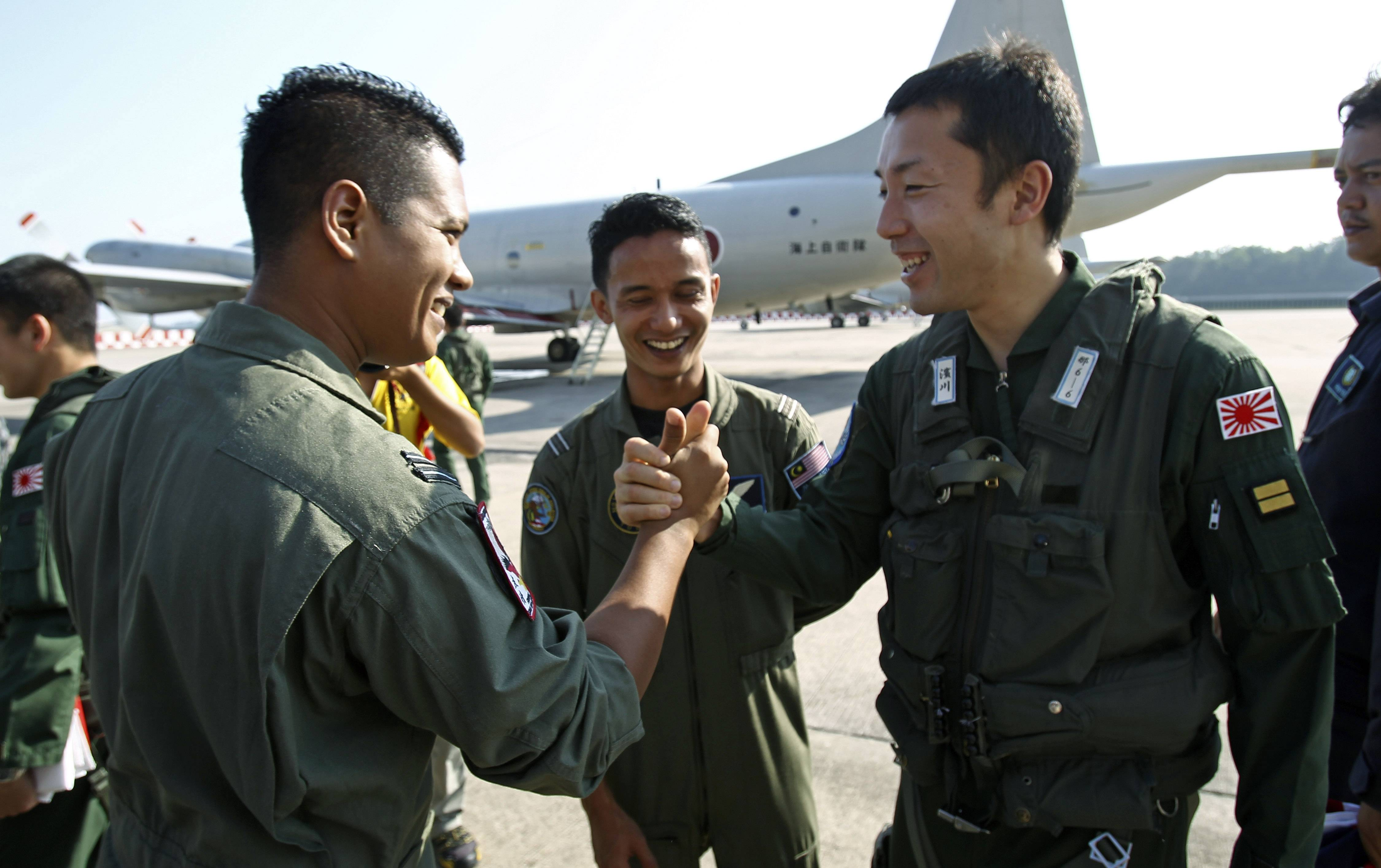 A crew member of Japan's Maritime Self-Defense Force, right, is wished well by a crew member of the Royal Malaysian Air Force before leaving the Royal Malaysian Air Force base for Australia to join a search and rescue operation for the missing Malaysia Airlines, flight MH370, in Subang, Malaysia Sunday. Search planes headed back out to a desolate patch of the southern Indian Ocean on Sunday in hopes of finding answers to the fate of the missing Malaysia Airlines jet, after China released a satellite image showing a large object floating in the search zone.