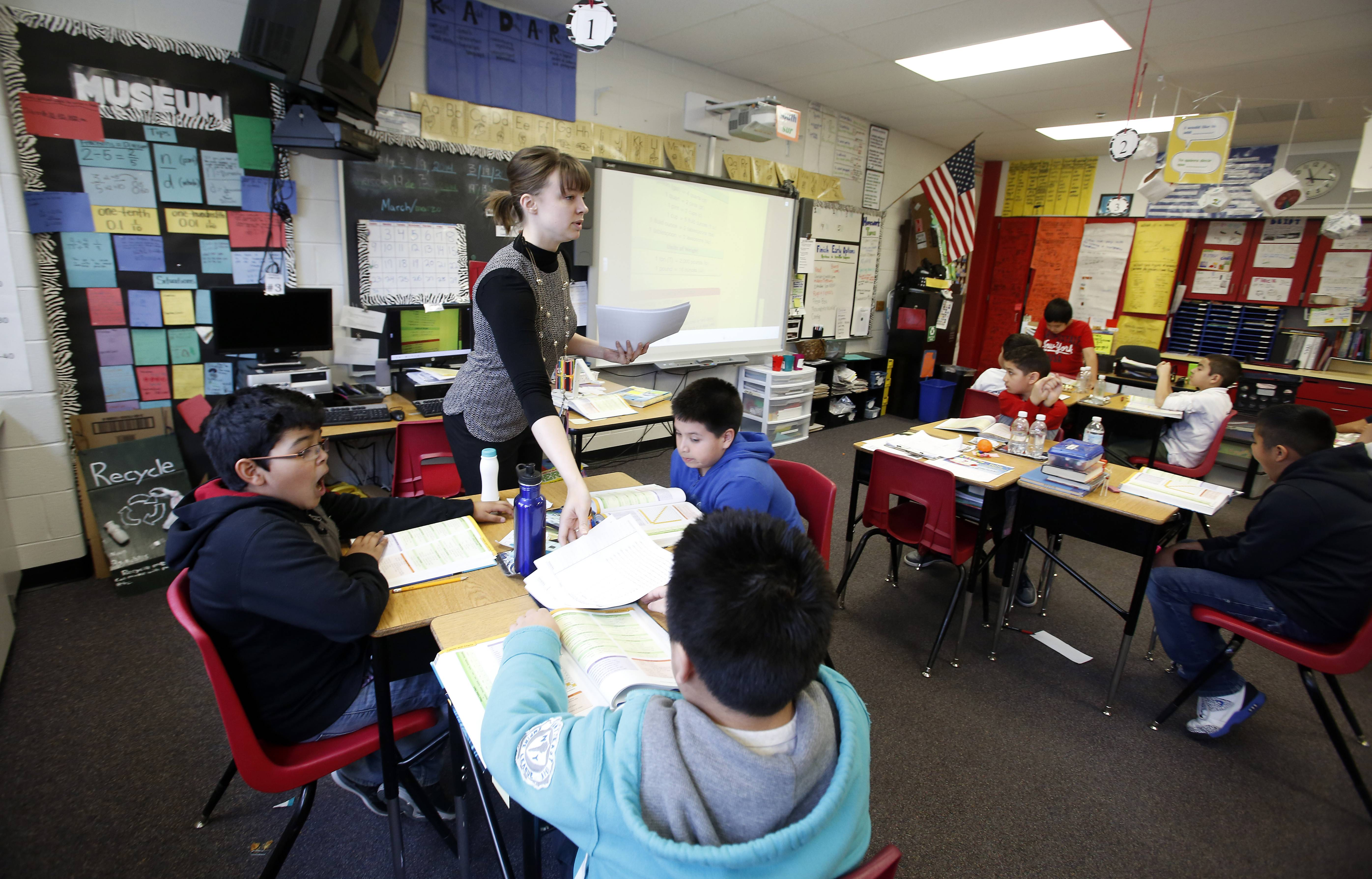 Kathryn Siscoe, a Spanish English Transition program teacher at Creekside Elementary School in Elgin, hands out papers to her fourth-grade students. U-46 will be eliminating all segregated fourth-grade gifted classrooms like this one next school year.
