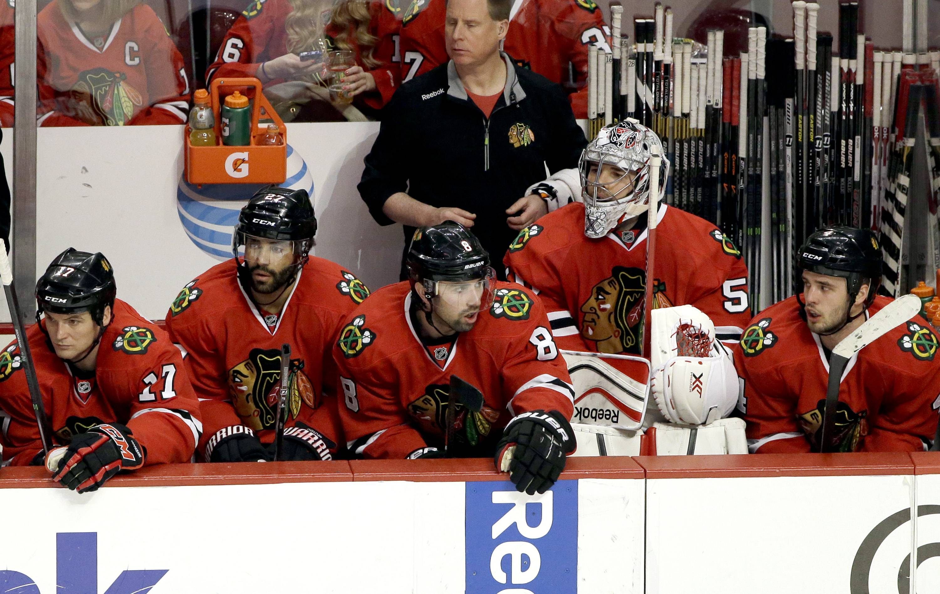 Chicago Blackhawks' Sheldon Brookbank (17), Johnny Oduya (27), Nick Leddy (8), goalie Corey Crawford (50), and Niklas Hjalmarsson (4) react as they watch teammates during the third period of an NHL hockey game against the Nashville Predators in Chicago, Sunday, March 23, 2014. The Predators won 2-0.