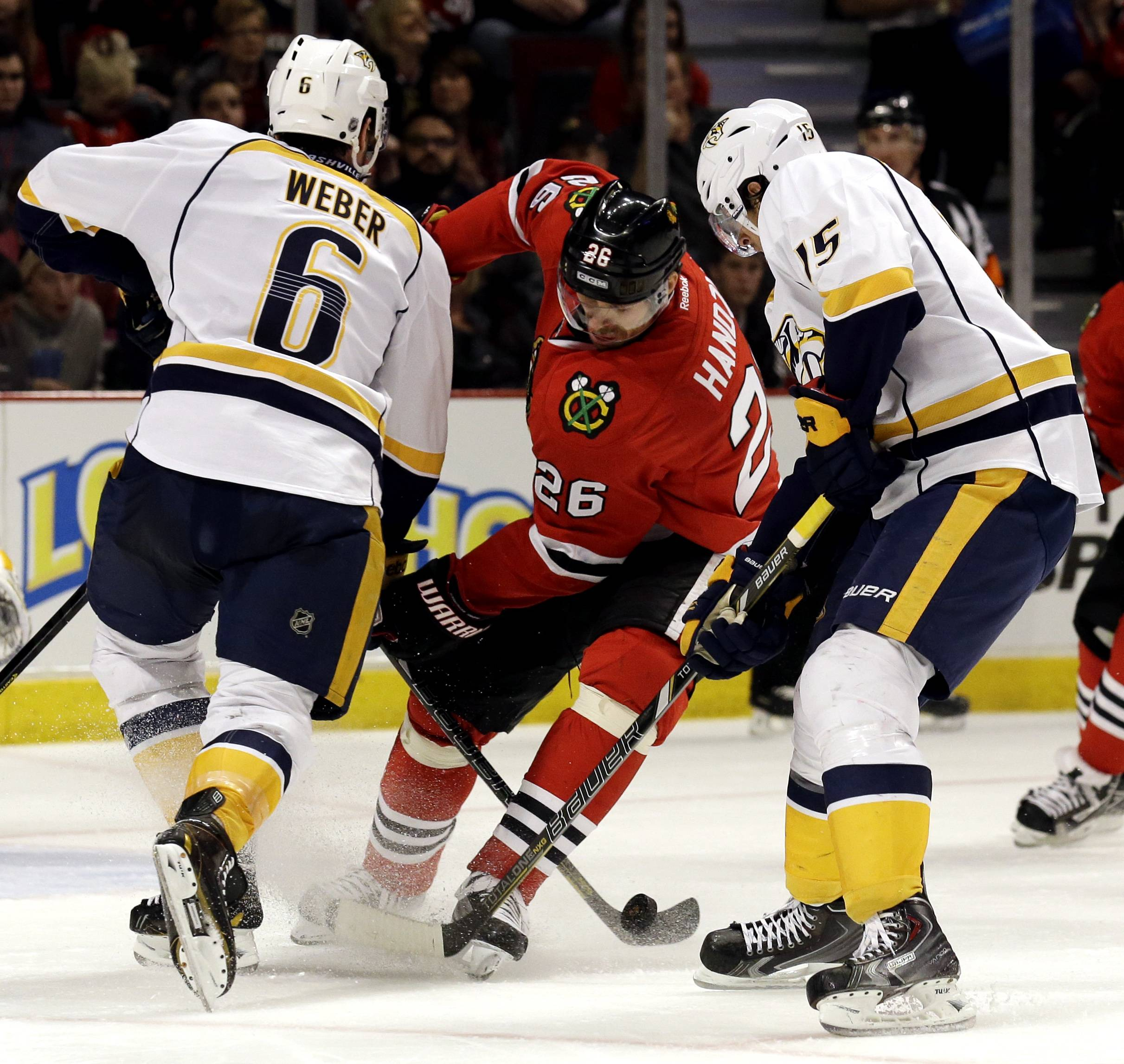 Chicago Blackhawks' Michal Handzus (26), center, battles for the puck against Nashville Predators' Shea Weber (6), left, and Craig Smith (15) during the second period of an NHL hockey game in Chicago, Sunday, March 23, 2014.