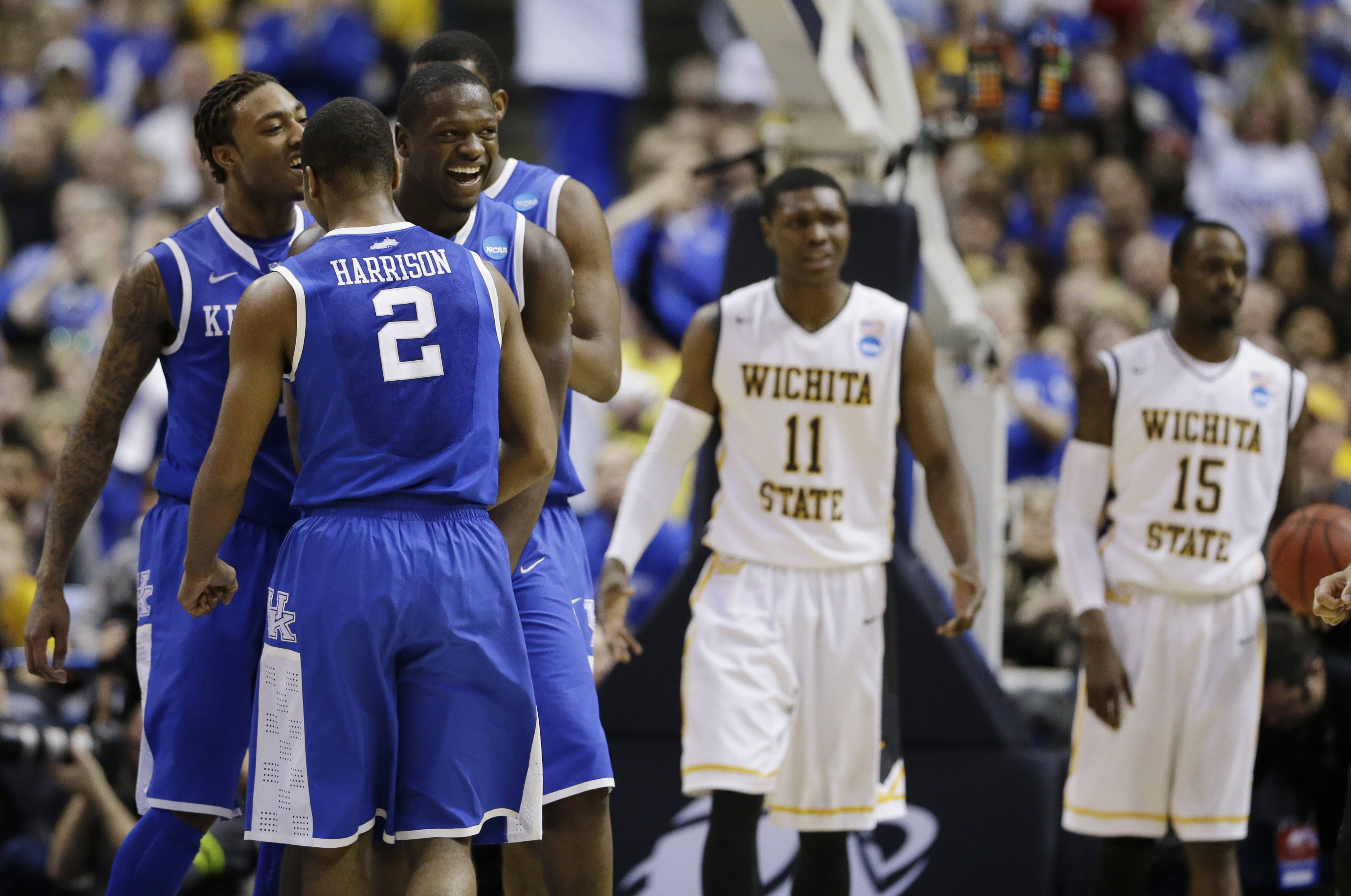 Kentucky players from left, guard/forward James Young (1), guard Aaron Harrison (2) and forward Julius Randle (30) celebrate against Wichita State during the second half of a third-round game of the NCAA college basketball tournament Sunday, March 23, 2014, in St. Louis.