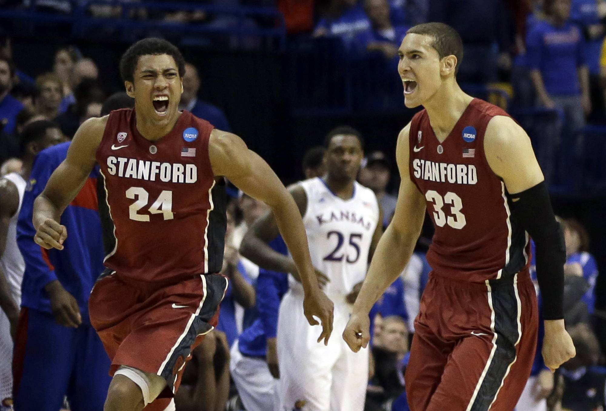 Stanford's Josh Huestis, left, and Dwight Powell, right, celebrate as Kansas' Tarik Black (25) watches in the background after in a third-round game of the NCAA college basketball tournament Sunday, March 23, 2014, in St. Louis. Stanford won 60-57.