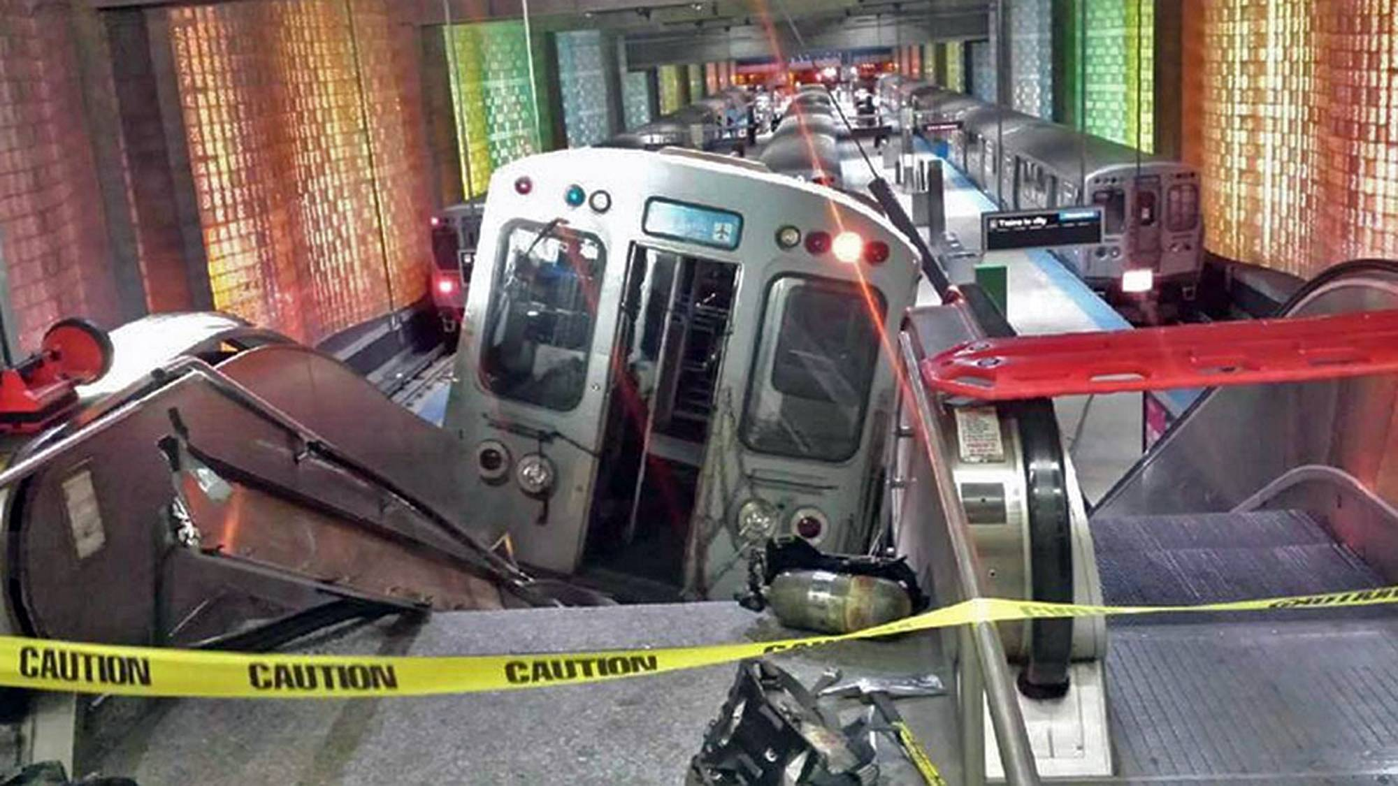 "A Chicago Transit Authority train car rests Monday on an escalator at the O'Hare Airport station after it derailed. More than 30 people were injured after the train ""climbed over the last stop, jumped up on the sidewalk and then went up the stairs and escalator,"" according to Chicago Fire Commissioner Jose Santiago."