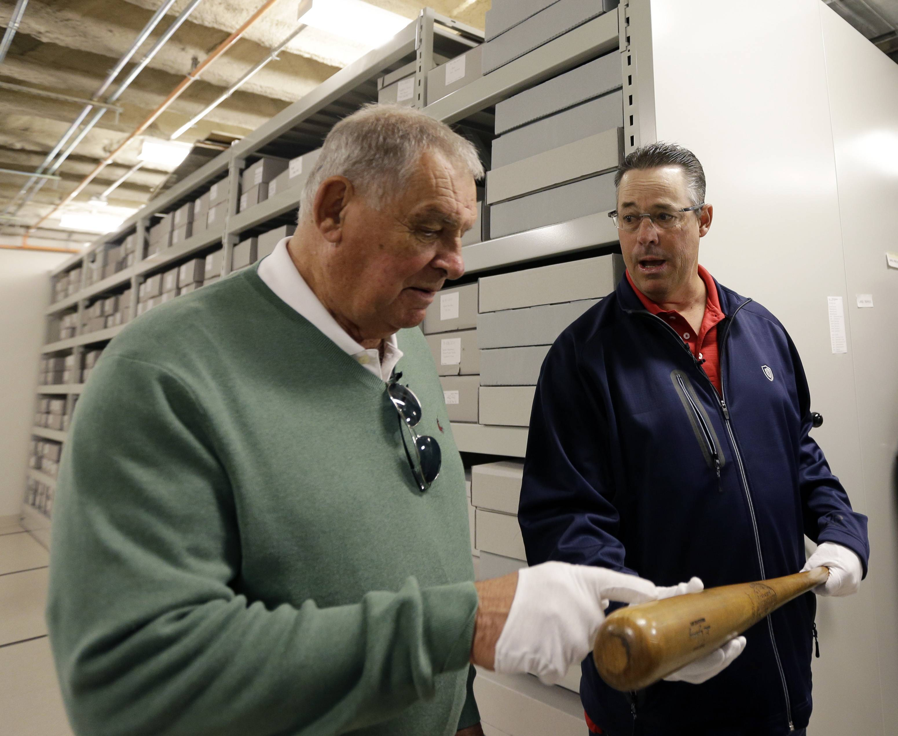 Former Atlanta Braves manager Bobby Cox, left, and former pitcher Greg Maddux hold a Lou Gehrig bat during their orientation visit at the Baseball Hall of Fame on Monday, March 24, 2014, in Cooperstown, N.Y. They will be inducted to the hall in July. (AP Photo/Mike Groll)
