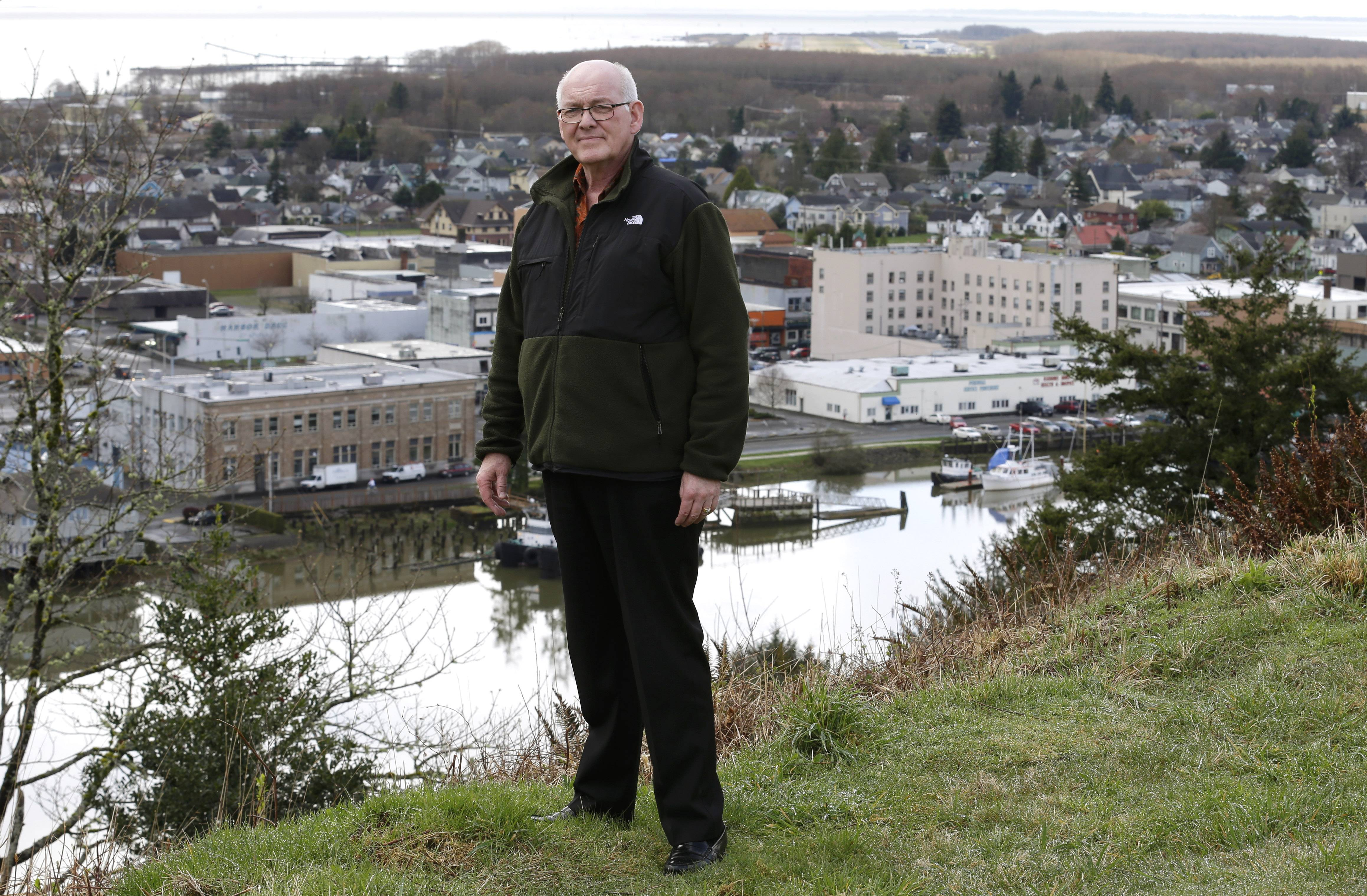 Jack Durney, mayor of Hoquiam, Wash., stands on a hill on Monday overlooking his city, the Hoquiam River, and Grays Harbor. Because most of Hoquiam lies in the flood plain, Durney says possible increases in federal flood insurance rates would adversely affect many who live in his town. In the old logging port on an estuarine bay, the great majority of the 8,700 residents live in a flood hazard area.