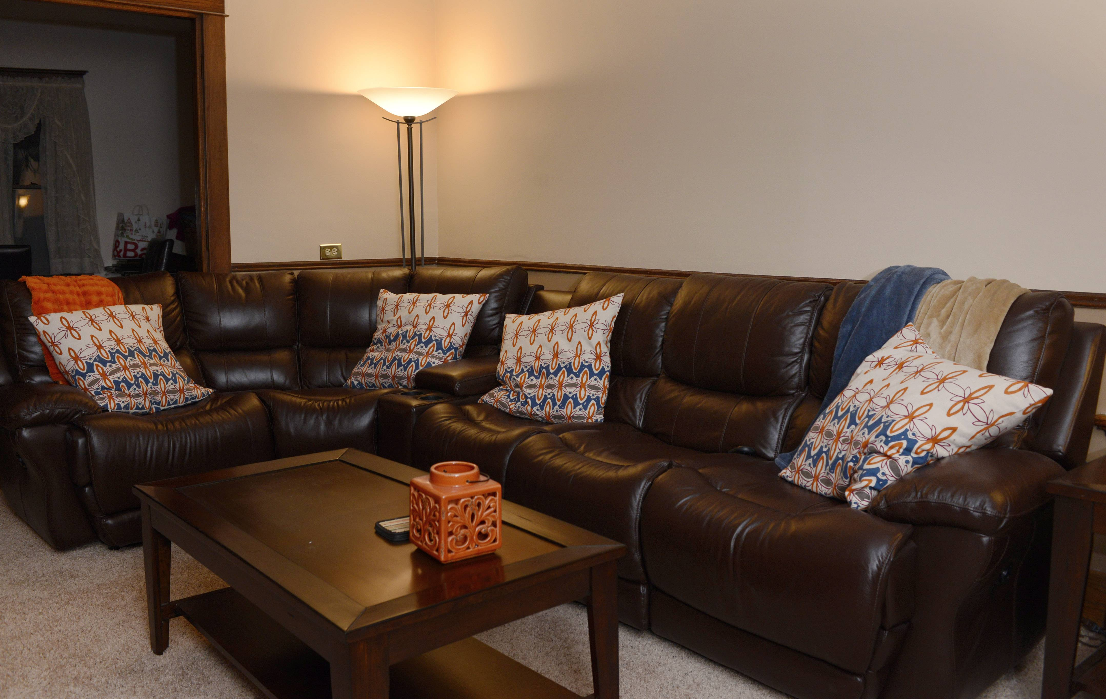 A brown leather sectional from O'Reilly's Furniture sports four power recliners, complete with cup holders, for the Browns' living room makeover.