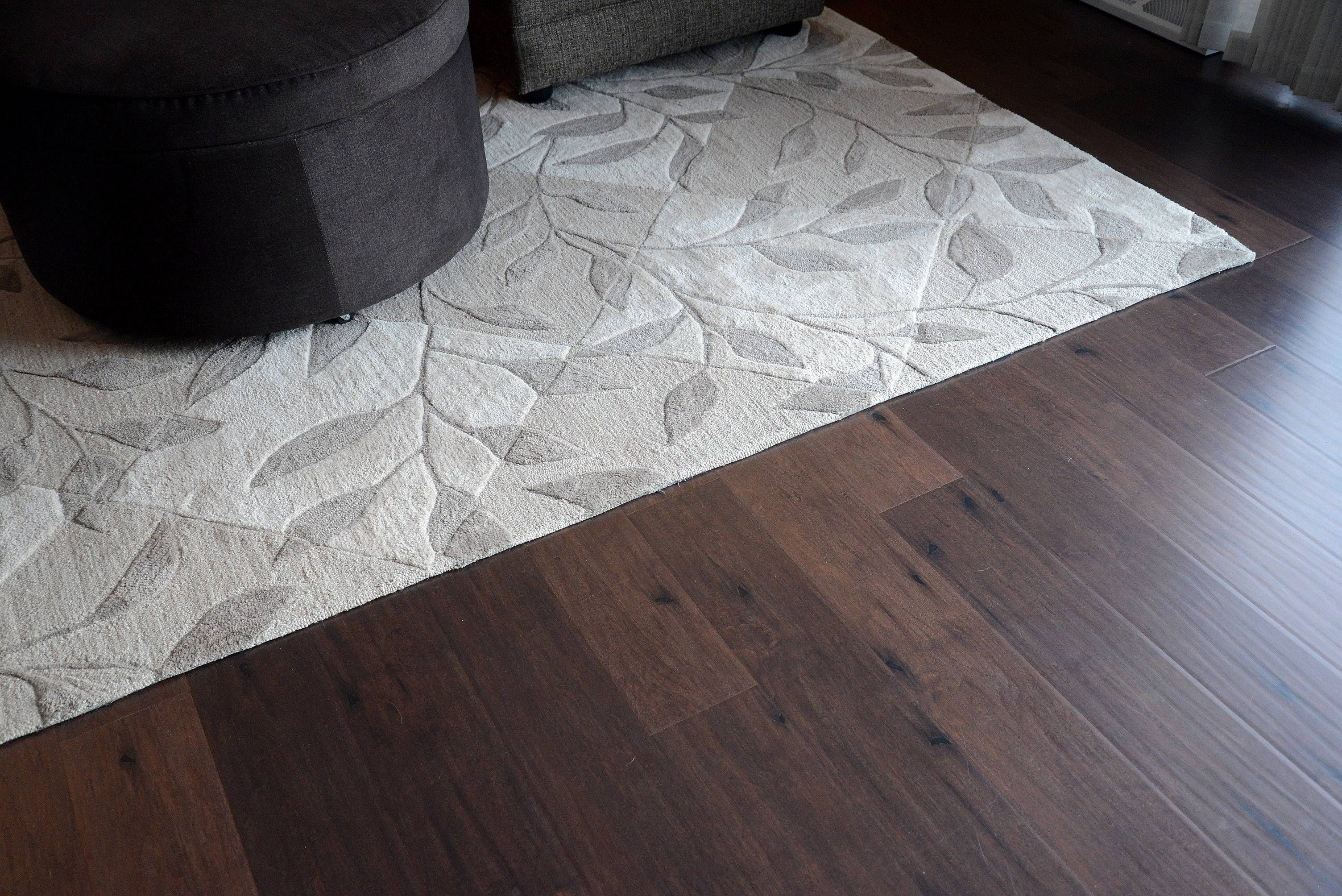 The Burcks replaced green shag carpeting with wide plank laminate flooring from Century Tile, toppped by an area rug in two shades of tan.