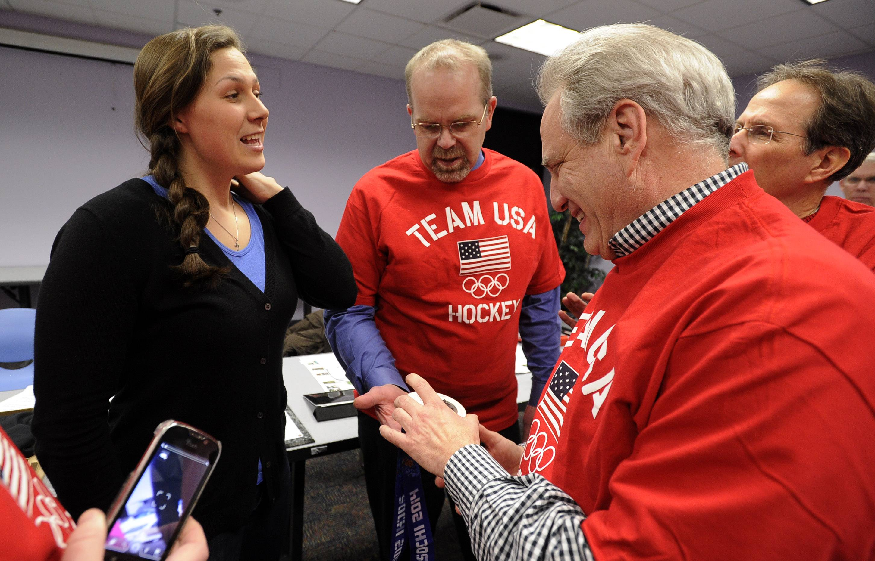 Buffalo Grove resident Megan Bozek is greeted by the members of the Buffalo Grove Park District Monday, Ryan Risinger, deputy director and Scott Jacobson, vice president on the district board where she proudly displayed her silver medal she won for the Winter Olympics hockey team in Sochi. She was honored for her achievements.