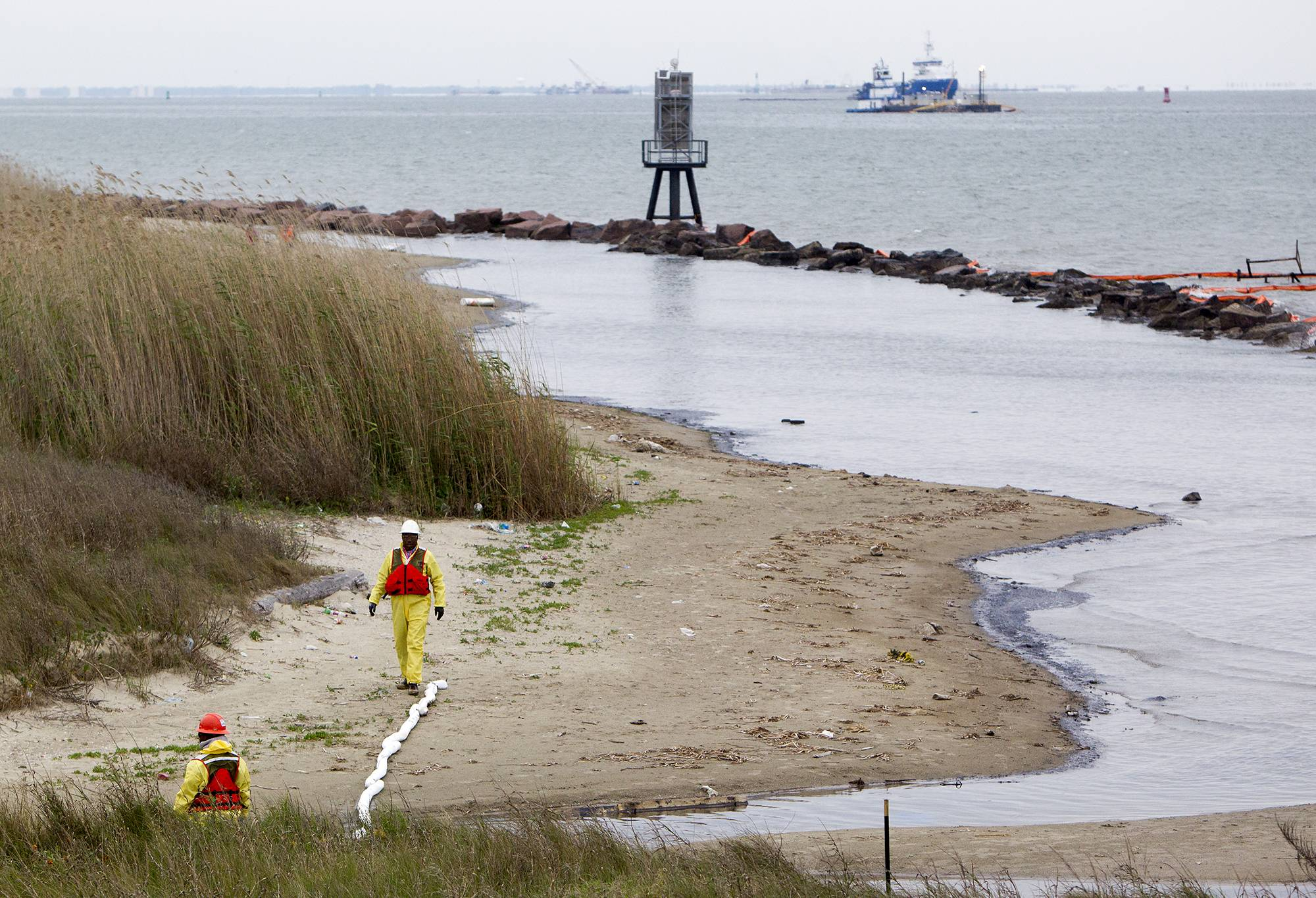Crews work to clean oil from the shore in Galveston, Texas, Monday after thousands of gallons of tar-like oil spilled into the major shipping channel after a barge ran into a ship Saturday.