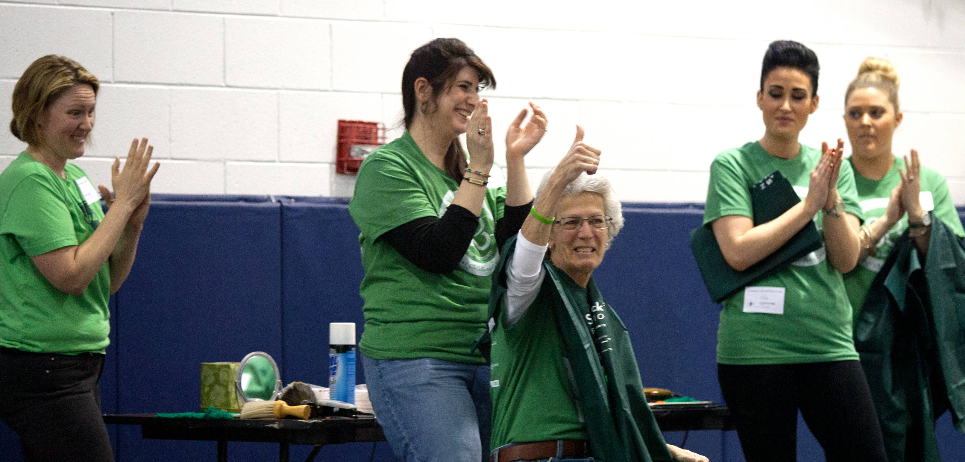 Nancy Shirley gives the thumbs-up before getting her head shaved Friday during a St. Baldrick's fundraiser at Madison Elementary School in Wheaton.