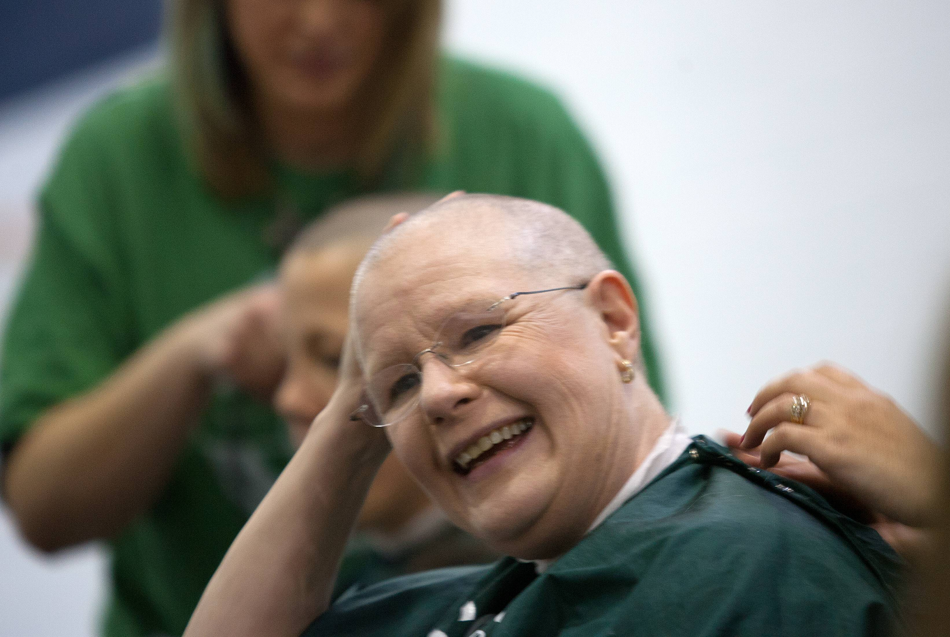 Pam Menzel scratches her head after getting her head shaved during a St. Baldrick's fundraiser Friday at Madison Elementary School in Wheaton.