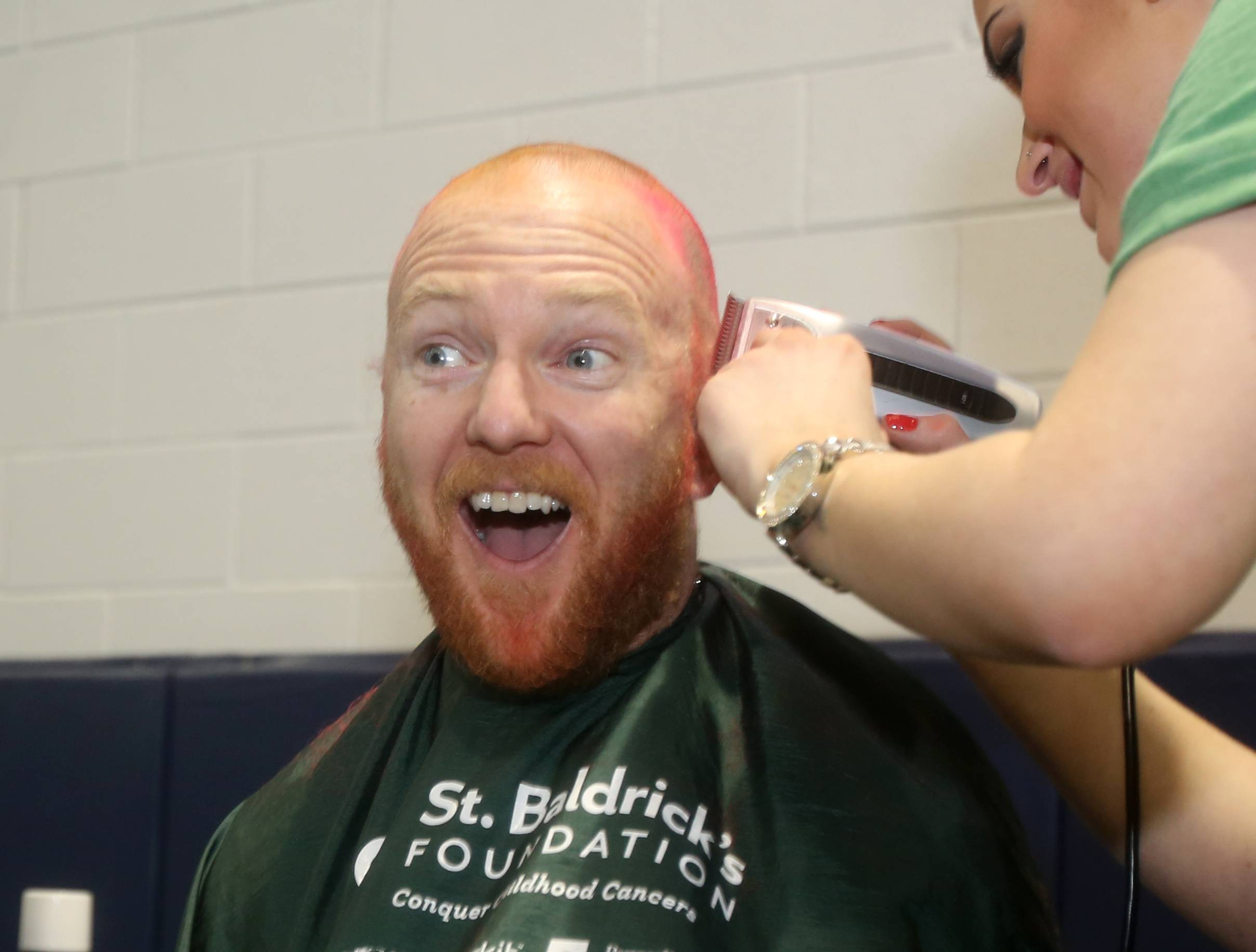 Principal Tim Callahan gets more than a trim during a St. Baldrick's fundraiser Friday at Madison Elementary School in Wheaton.