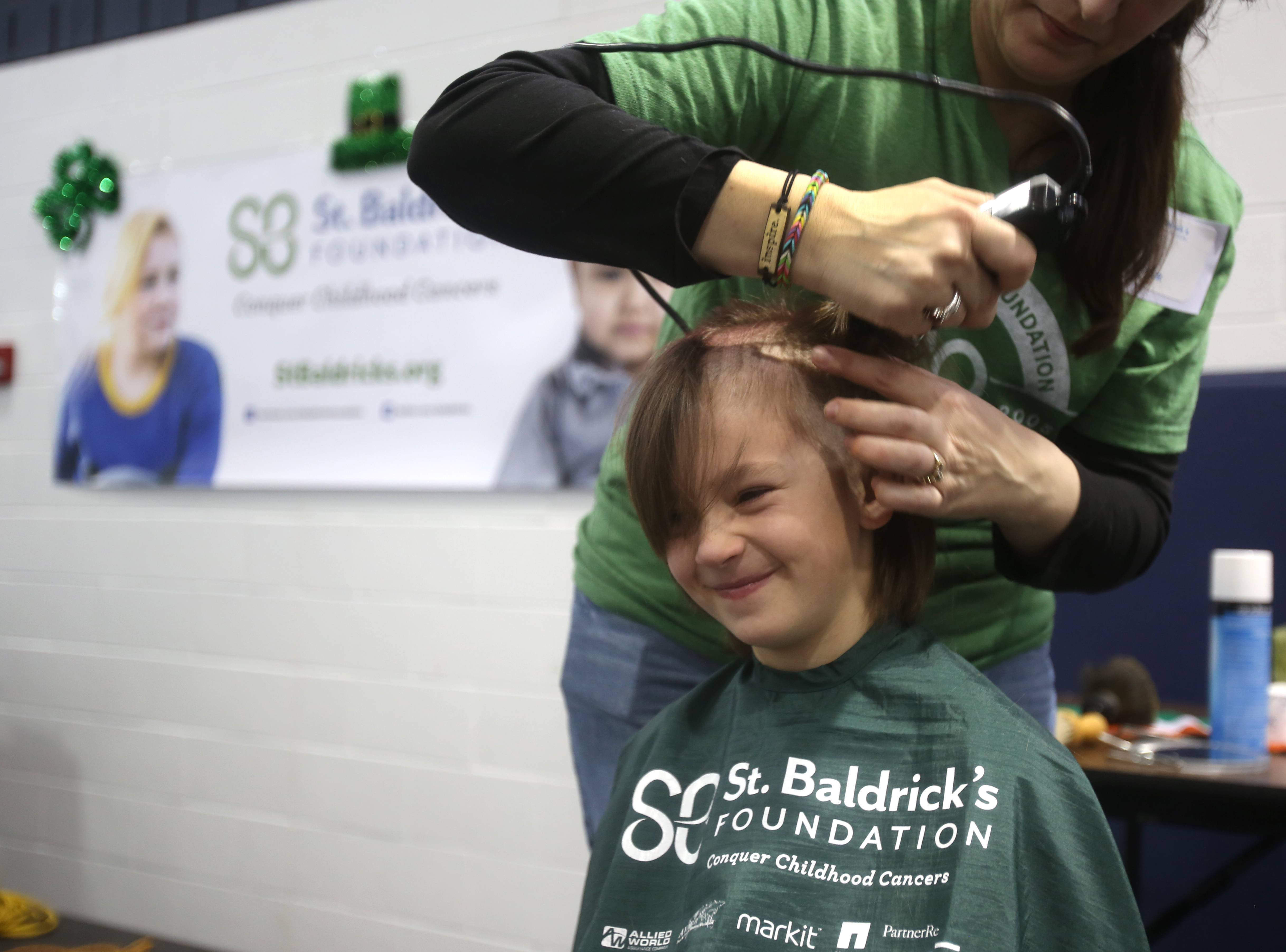 Ezra Mouw gets a haircut during a St. Baldrick's fundraiser Friday at Madison Elementary School in Wheaton.