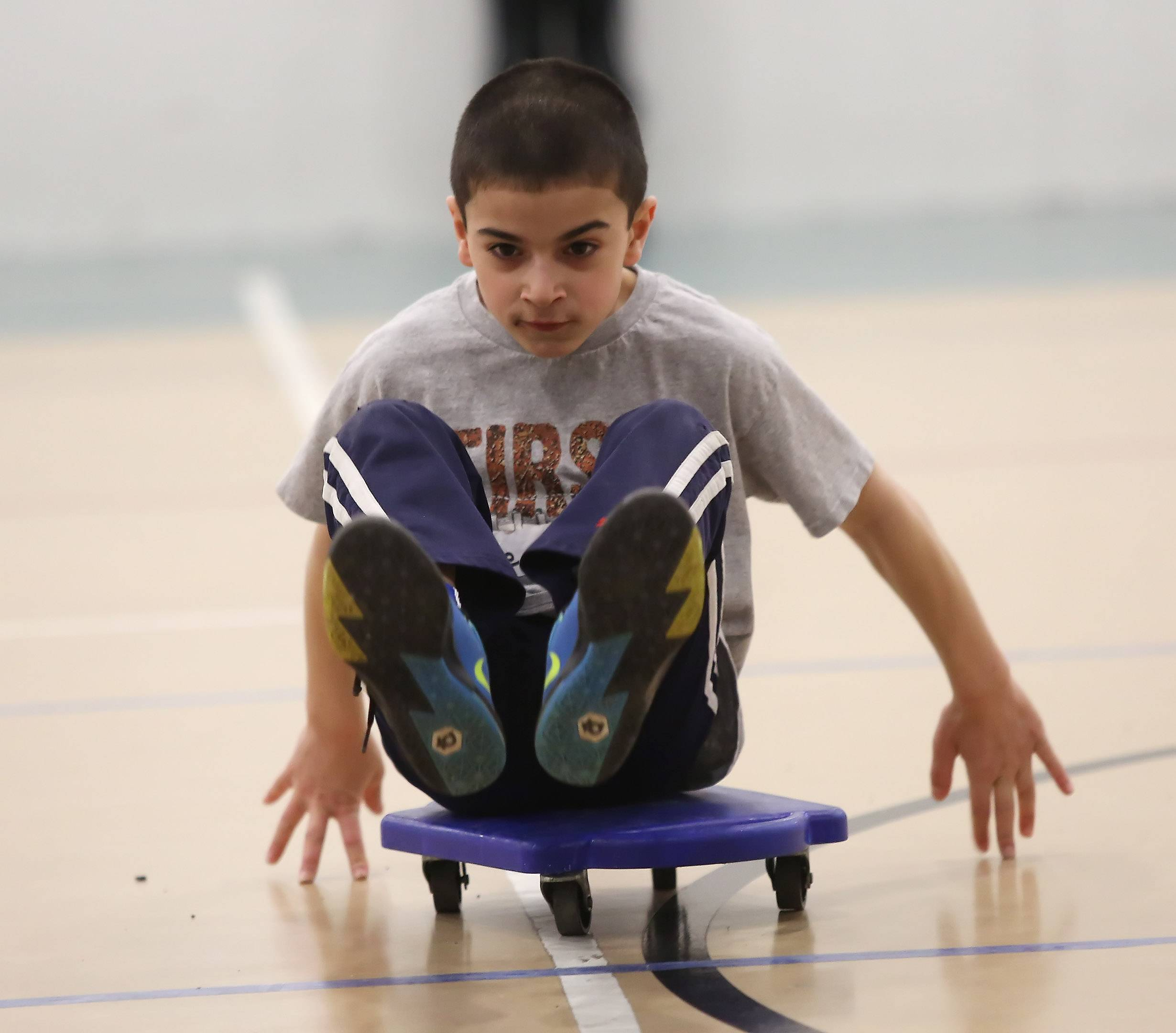 Kyle Lynch, 8, of Vernon Hills, participates in scooter races Monday during Days Off From School Camp at the Libertyville Sports Complex. Children in kindergarten through sixth grade spent the first day of spring break playing games and various sports, including climbing the rock wall.
