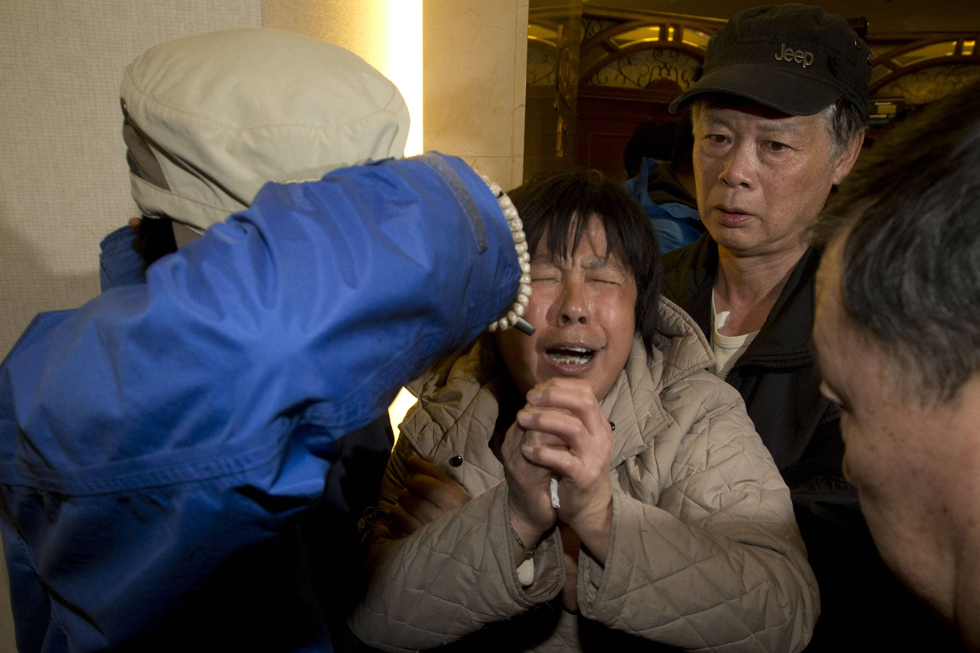 A relative of Chinese passengers aboard the Malaysia Airlines MH370 cries Monday after being told the latest update in Beijing, China. A new analysis of satellite data indicates the missing Malaysia Airlines plane crashed into a remote corner of the Indian Ocean, Malaysian Prime Minister Najib Razak said Monday.