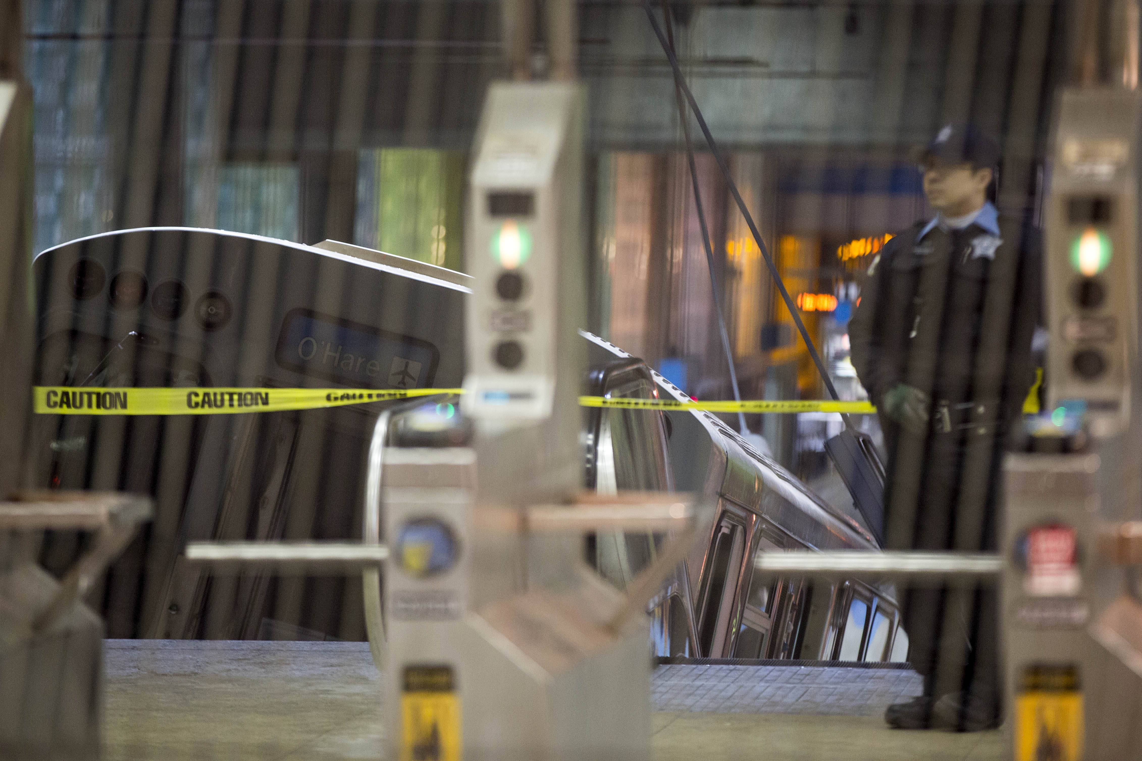 A police officer stands Monday near a Chicago Transit Authority train car that derailed at the O'Hare Airport station. More than 30 people were injured after the eight-car train plowed across a platform and scaled an escalator at the underground station.
